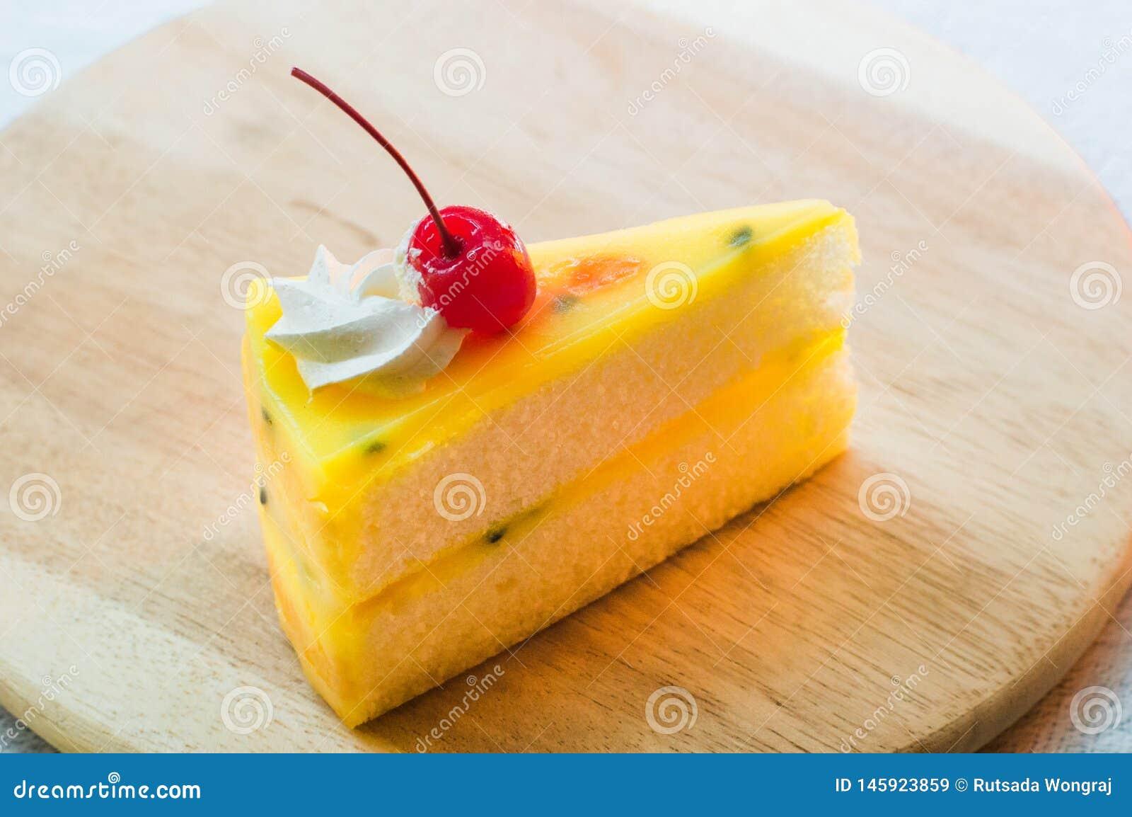 Sobremesa fresca do bolo do fruto de paixão na placa de madeira