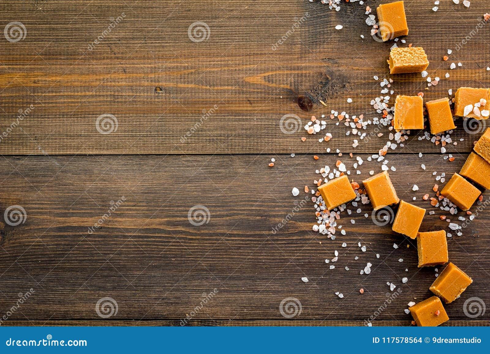Sobremesa na moda Caramelo salgado Cubos do caramelo polvilhados por cristais de sal no espaço de madeira escuro da opinião super