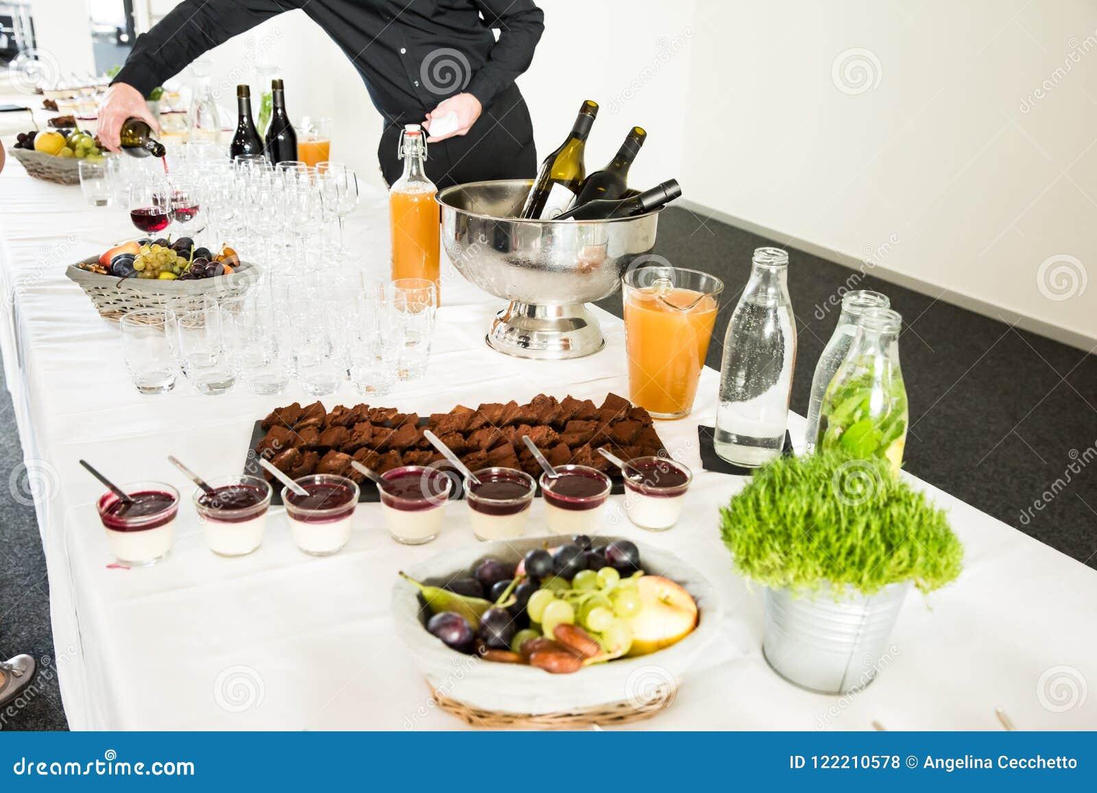 Sobremesas da restauração na tabela de bufete com vinho do serviço do homem no B