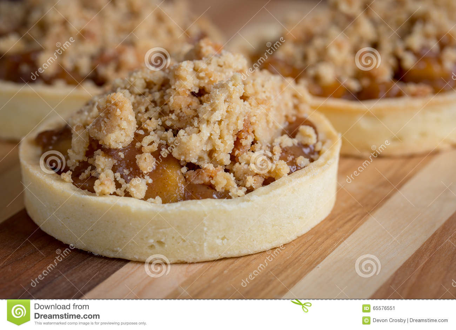 Sobremesas pequenas do tarte de maçã na placa de corte de madeira