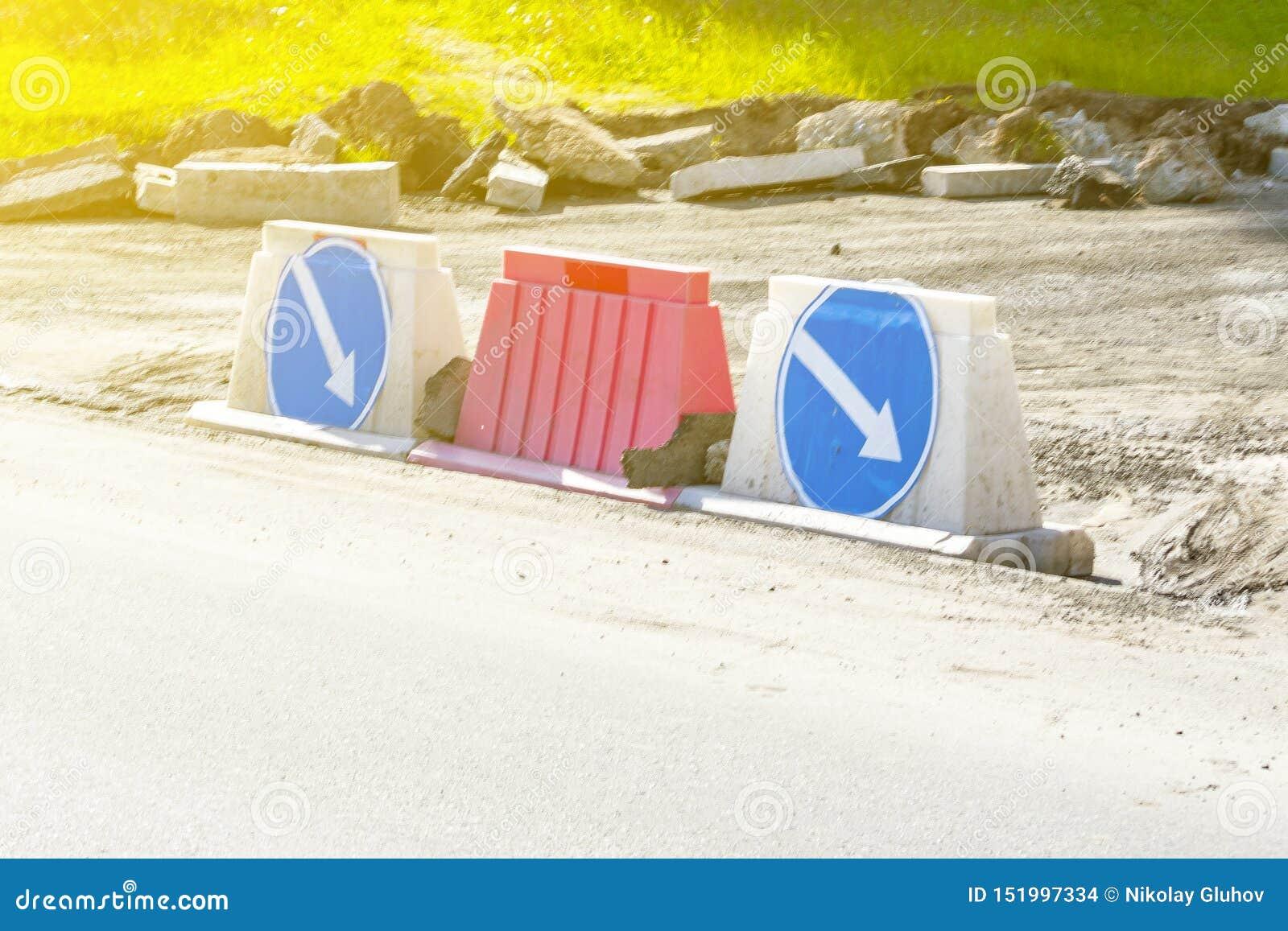 Sobreposições dos postes de amarração da estrada e sinais de estrada plásticos com setas em um fundo azul - rodeio à direita