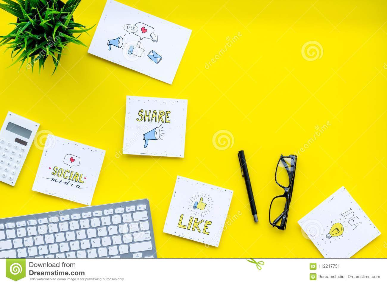 Socail media icons on work desk of marketing expert. Digital promotion of goods and services. Yellow background top view