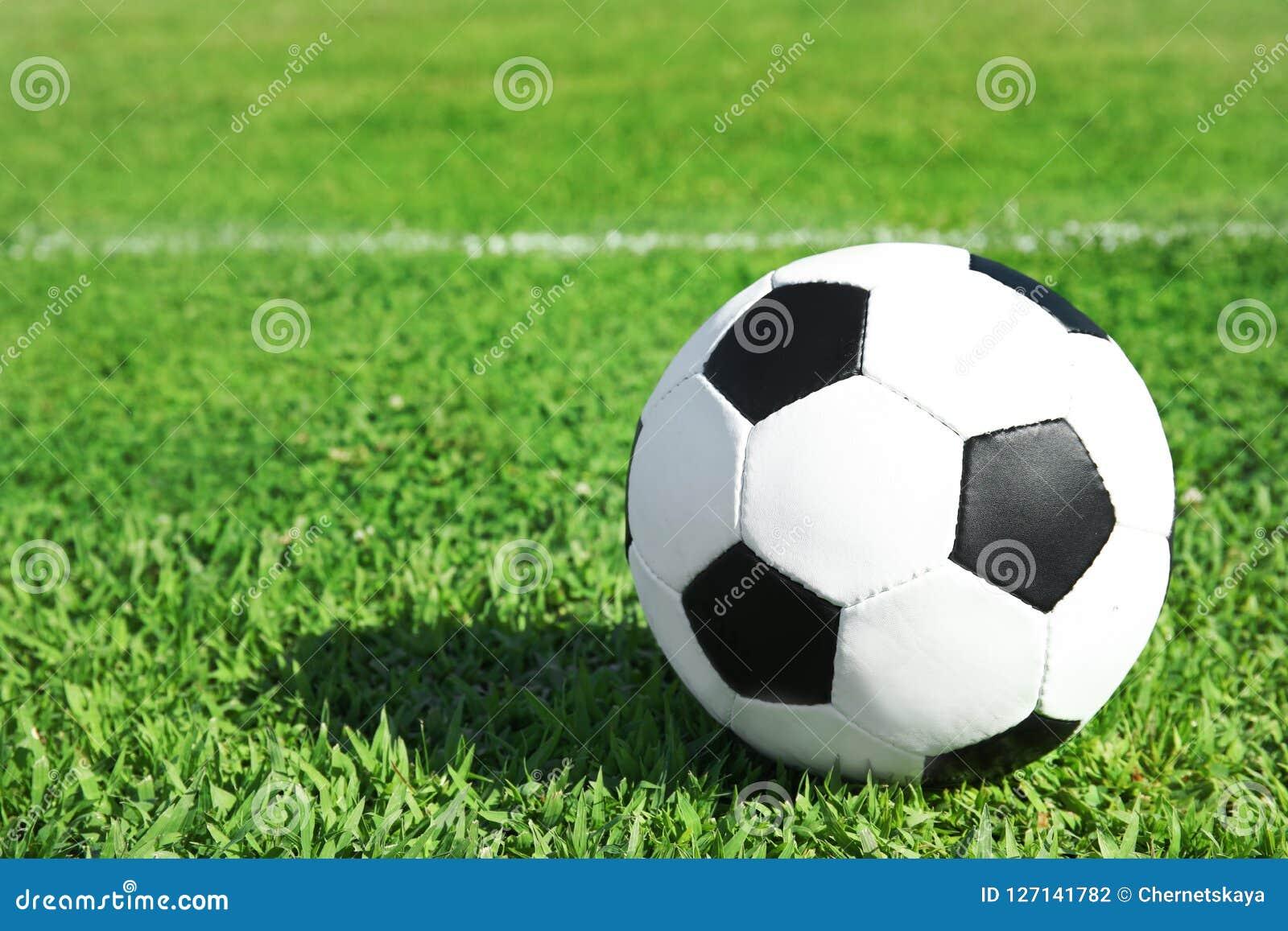 Soccer ball on fresh green football field grass.