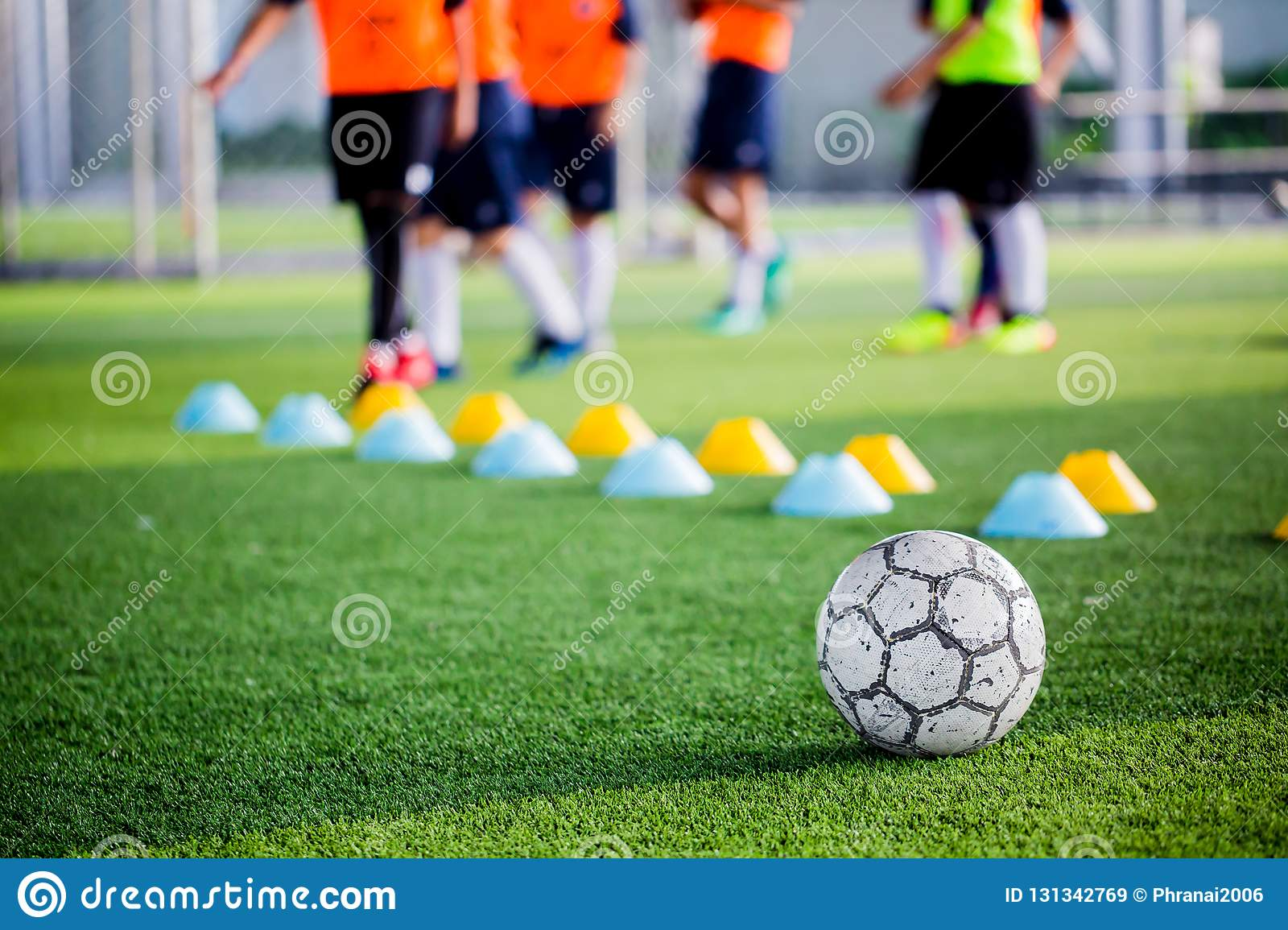 Soccer ball on green artificial turf with blurry of maker cones