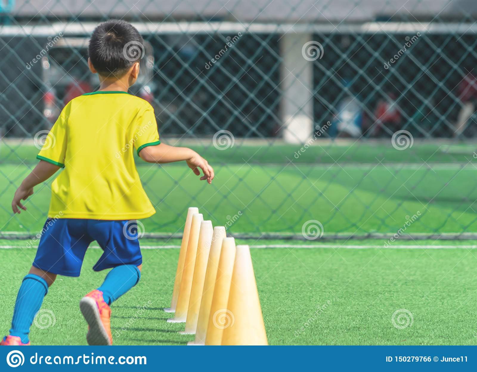 Soccer Boy training alone with cone on training ground