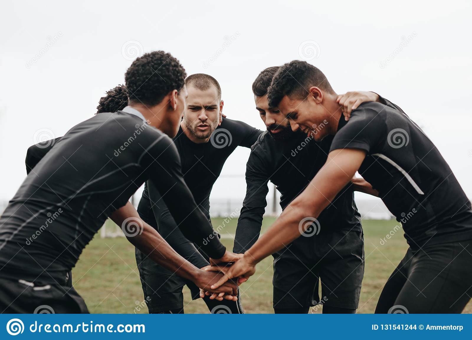 Soccer players joining hands in huddle talking about the game strategy. Footballers bending forward in a huddle holding hands