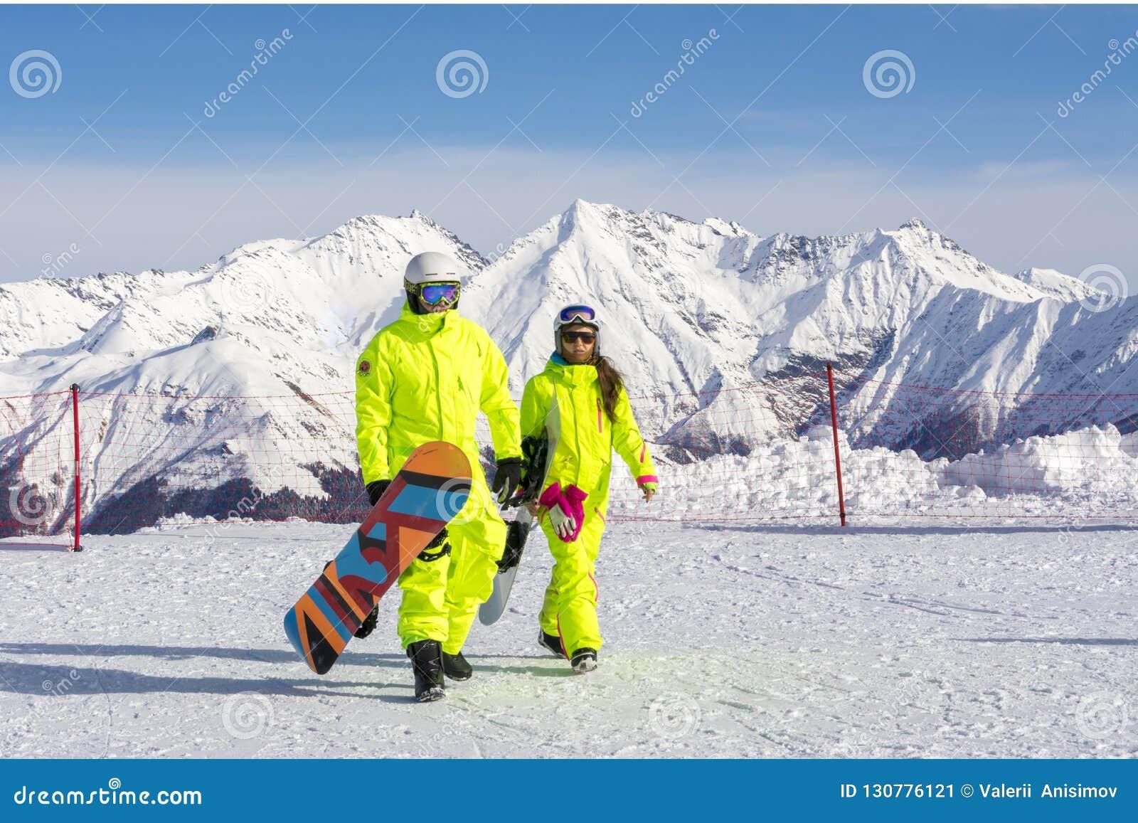 Sochi Ryssland, 11-01-2018 Rosa Khutor skidar semesterorten Snowboarders i ljusa dräkter av det rosa maximumet på en höjd av 2320