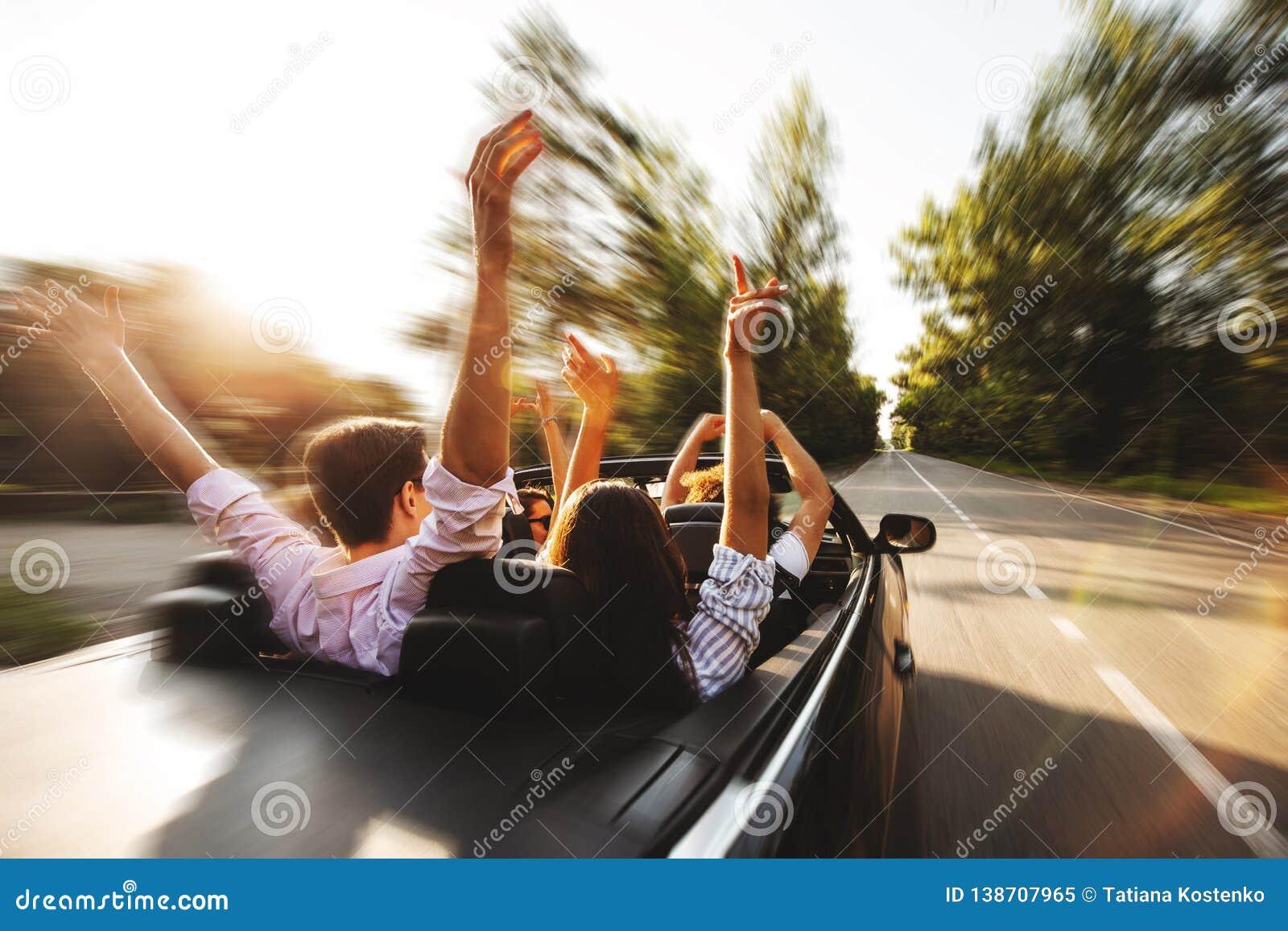 Société des jeunes montant dans un cabriolet sur la route et ho
