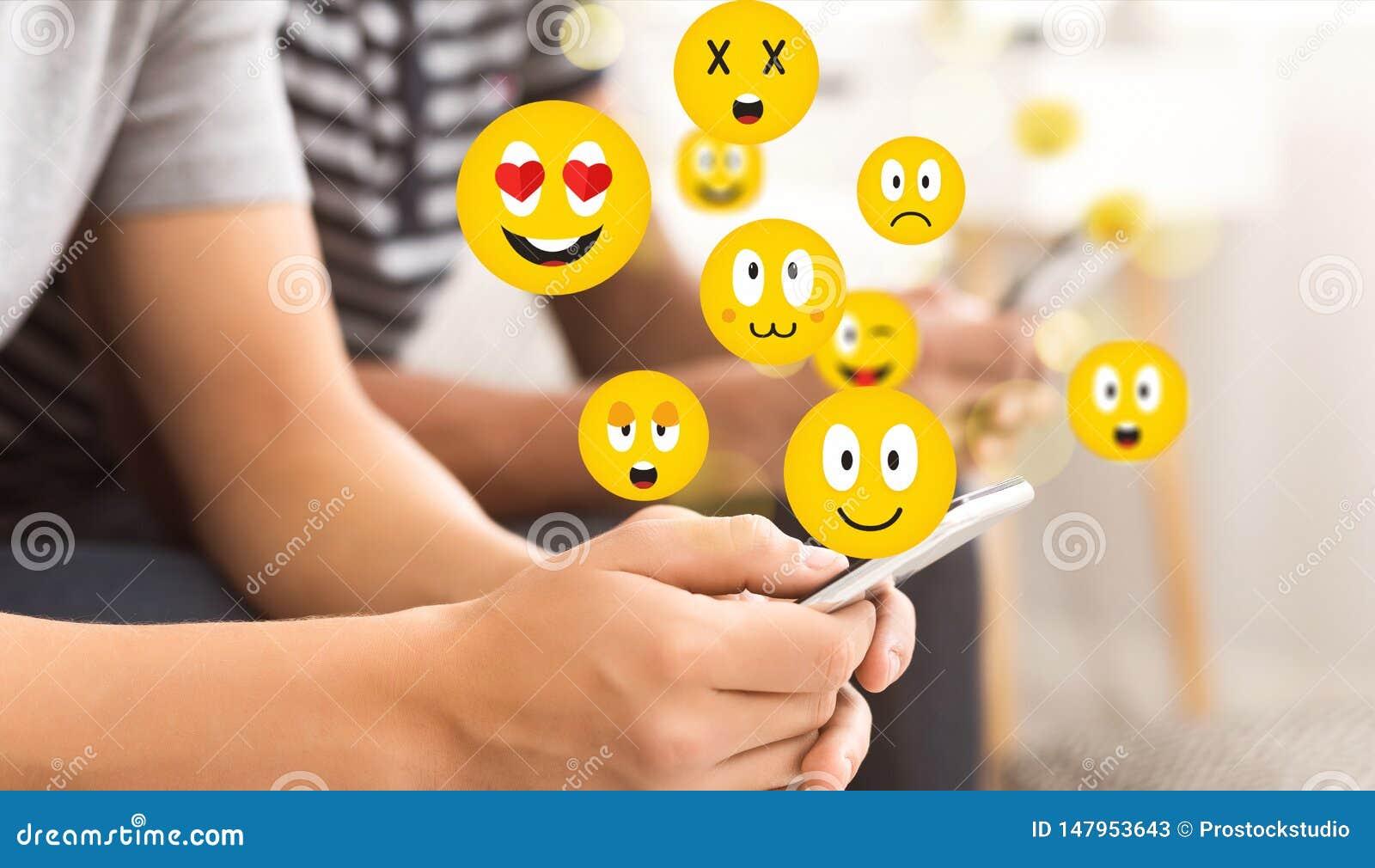 Sociaal concept Tienerkerel die smartphone gebruiken die emojis verzenden