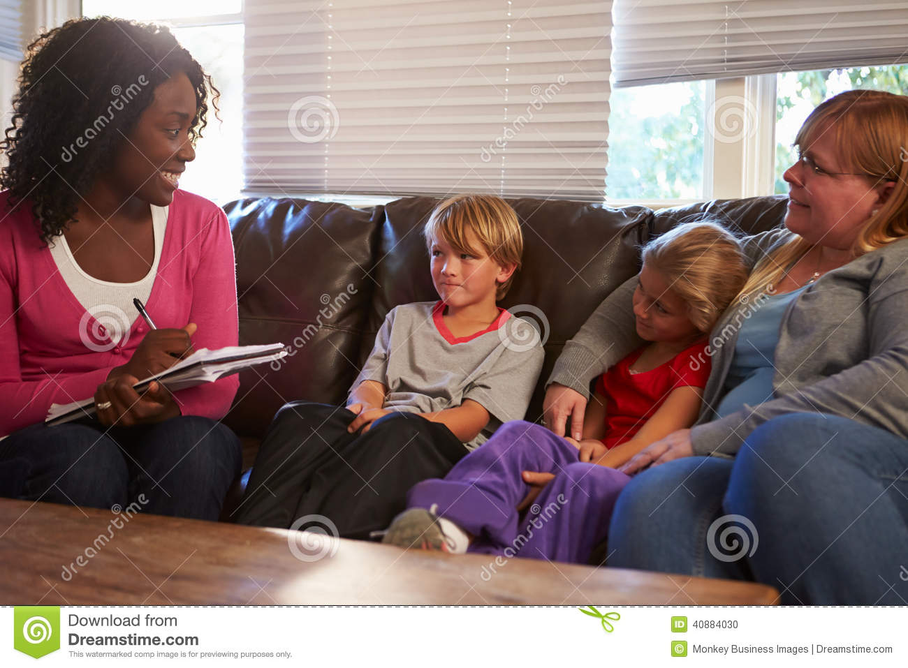 Social Worker Talking To Mother And Children At Home Stock