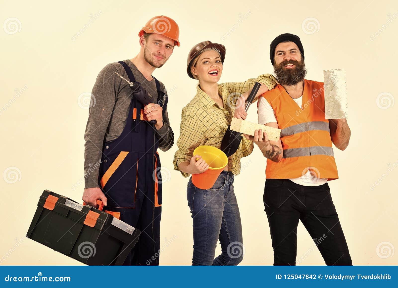 Società dei lavoratori allegri, costruttore, riparatore, intonacatore Uomo e donna con i fronti sorridenti in casco e nel boilers