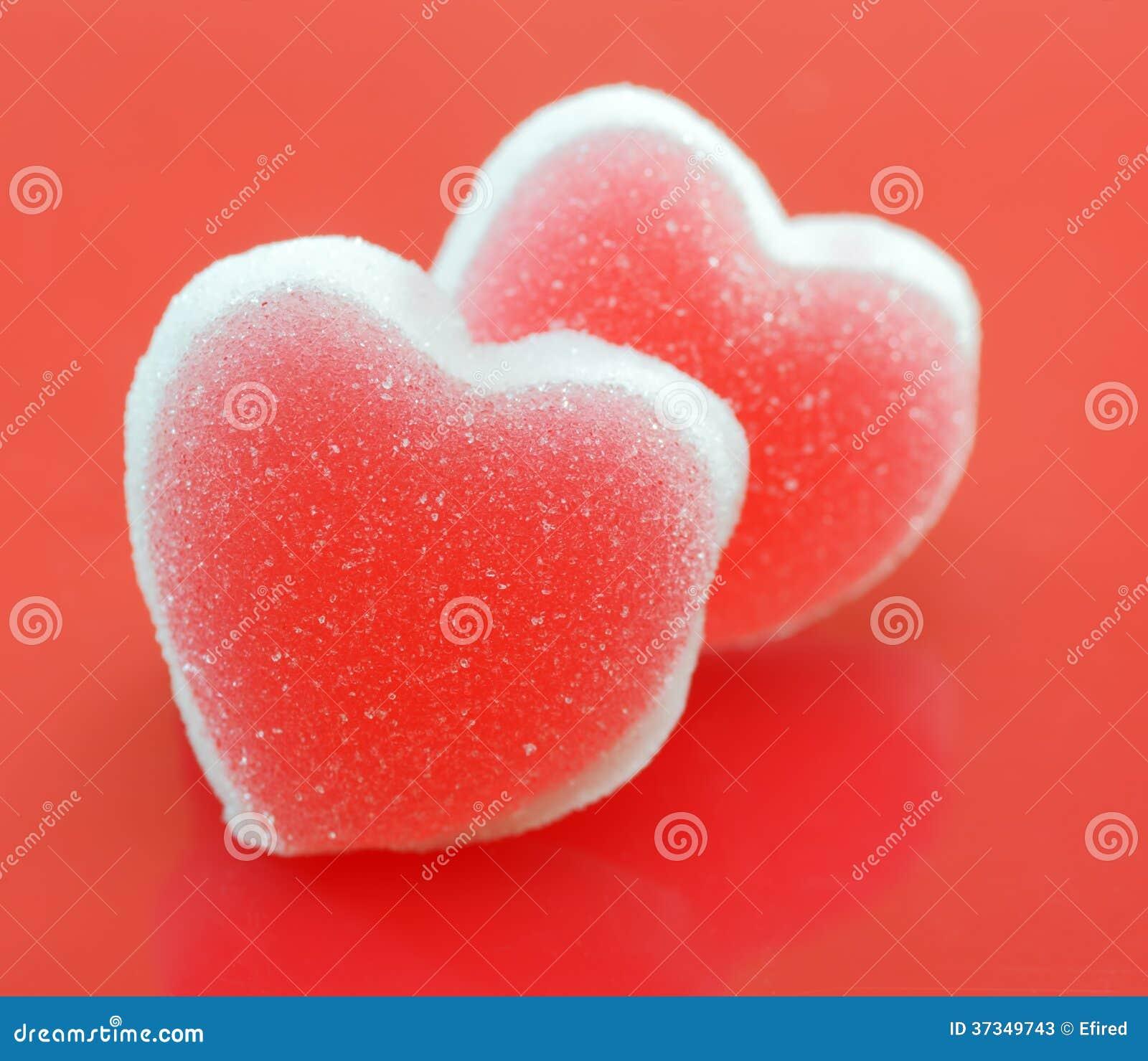 Sockerhjärtor på röd bakgrund