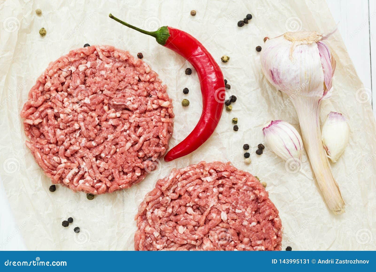Soczyści surowi hamburgery robić od organicznie mięsa na białym drewnianym tle z pikantność Odg?rny widok