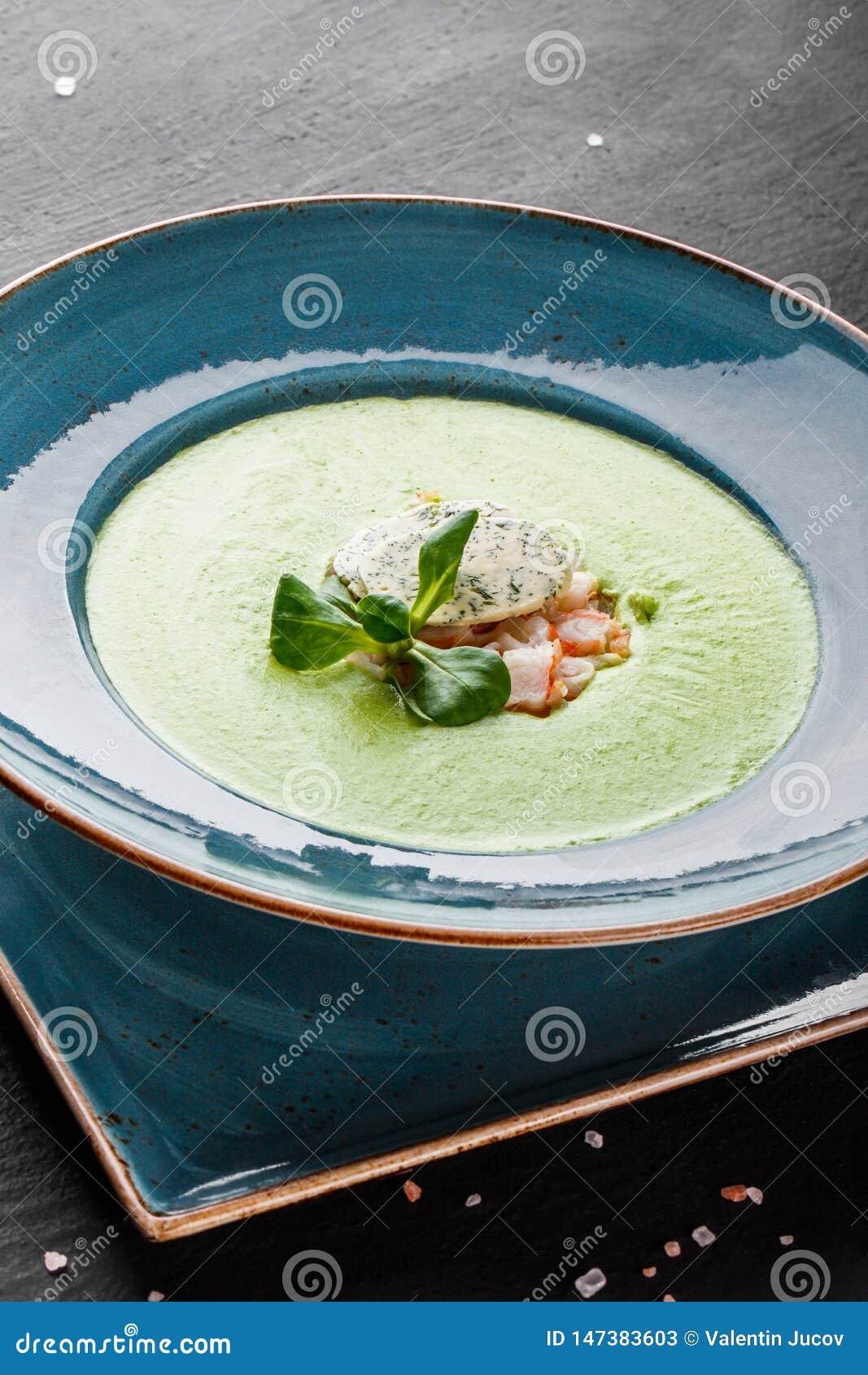 Soep van de broccoli de groene room met garnalen en kaas in plaat op donkere steenachtergrond Het schone eten, gezond voedselconc