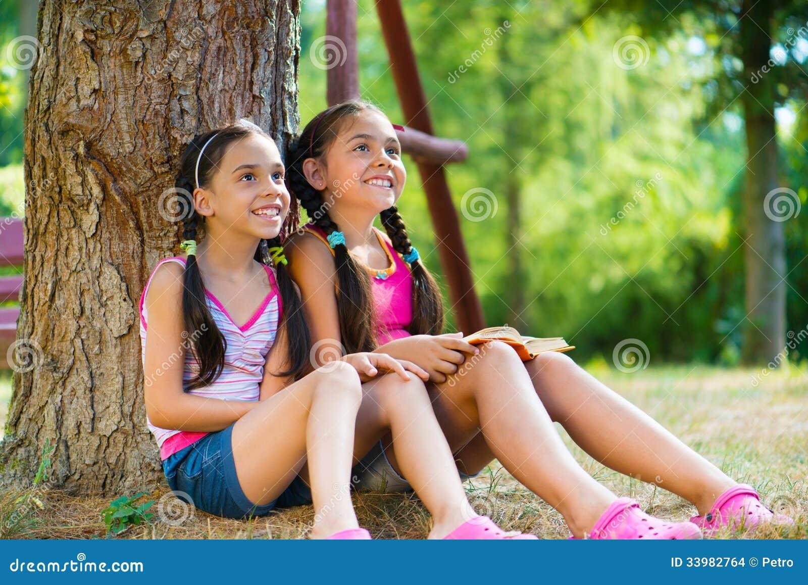 Soeurs hispaniques s asseyant sous l arbre et parler