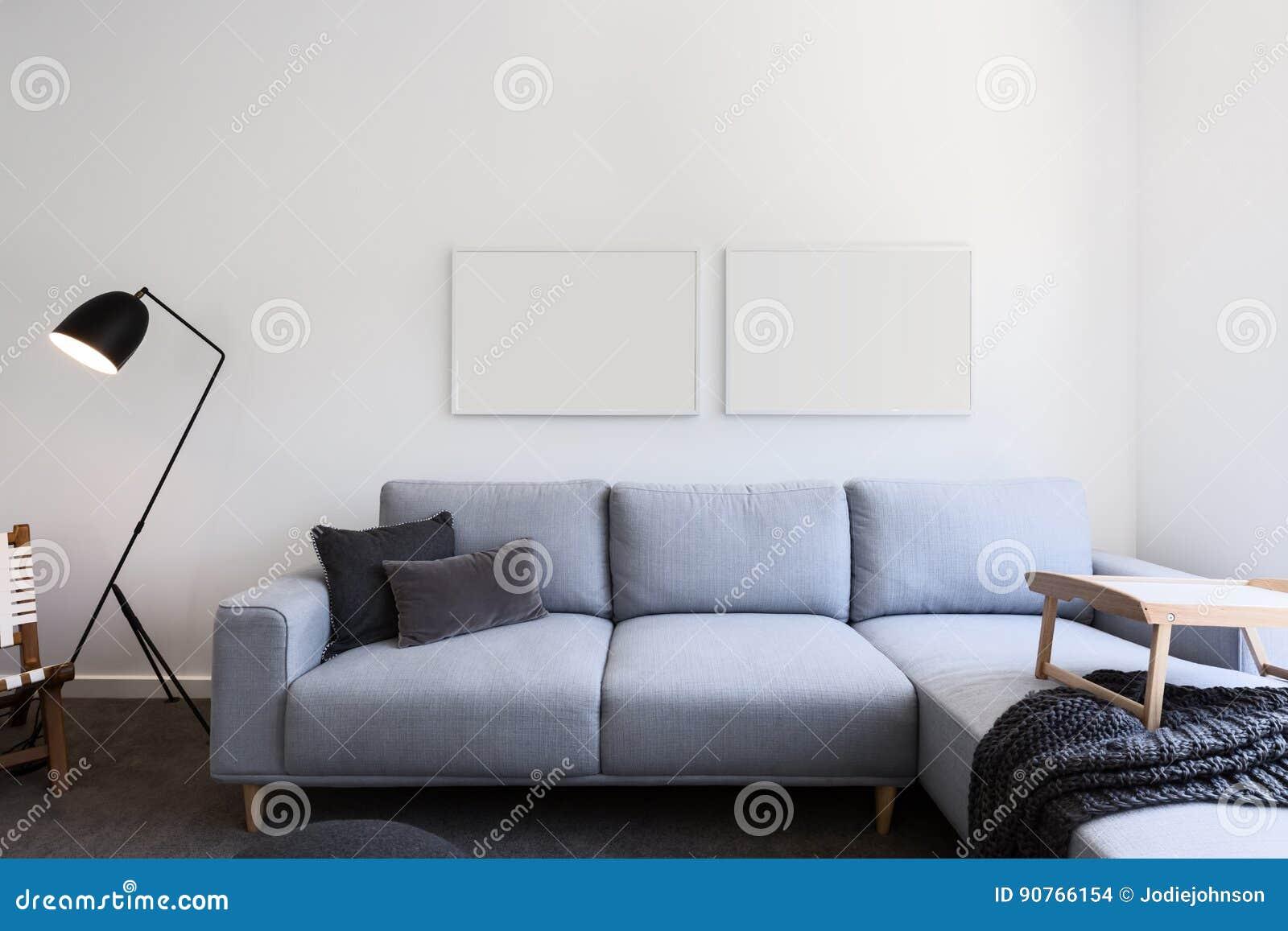 Sofà di tela blu-chiaro ed immagini in bianco in un salone