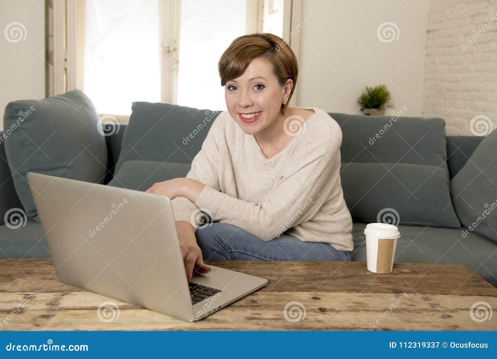 Sofá atrativo e feliz novo do sofá da mulher em casa que faz algum sorriso do trabalho do laptop relaxado no estilo de vida do em
