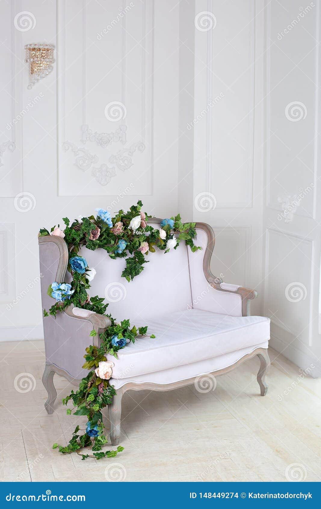 Sofá clásico de la materia textil ligera en un cuarto del vintage un interior real clásico ligero con un sofá suave con una tapic