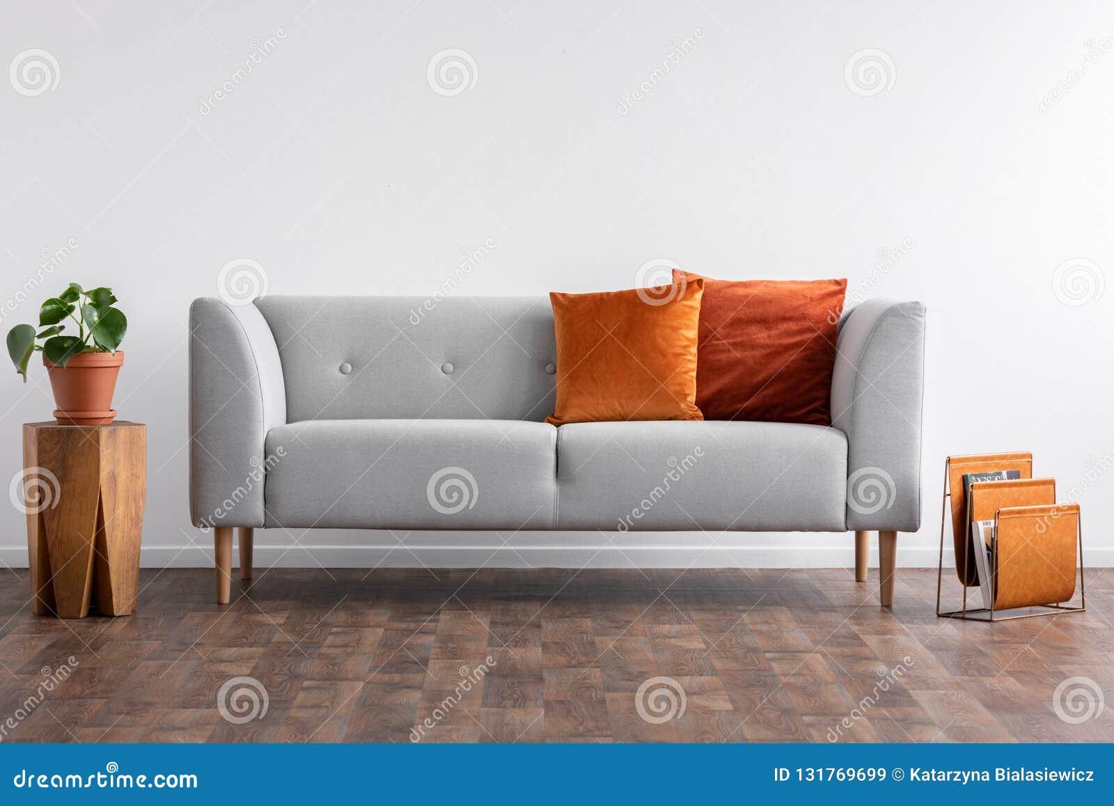 Sofá com os descansos entre a tabela e o organizador de madeira do jornal, foto real com espaço da cópia no branco vazio