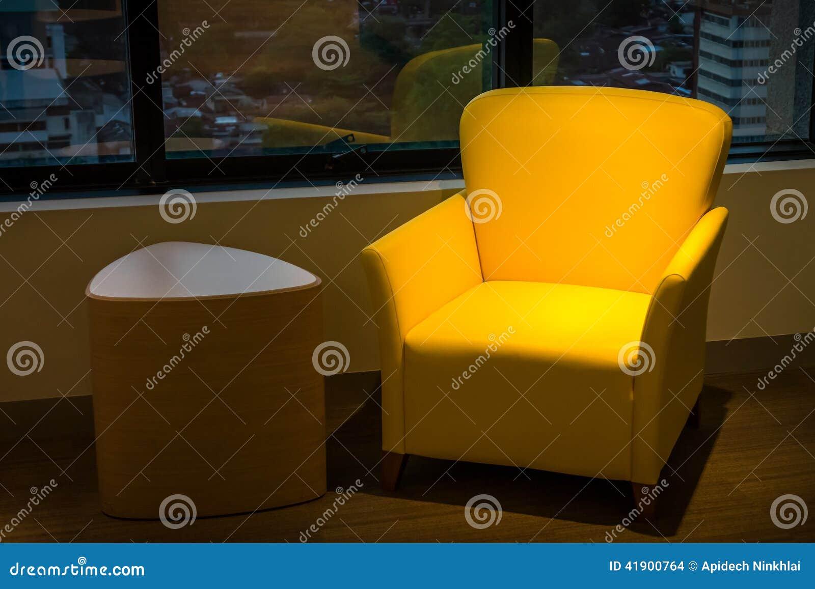 Sofá de cuero amarillo y tabla de madera lateral