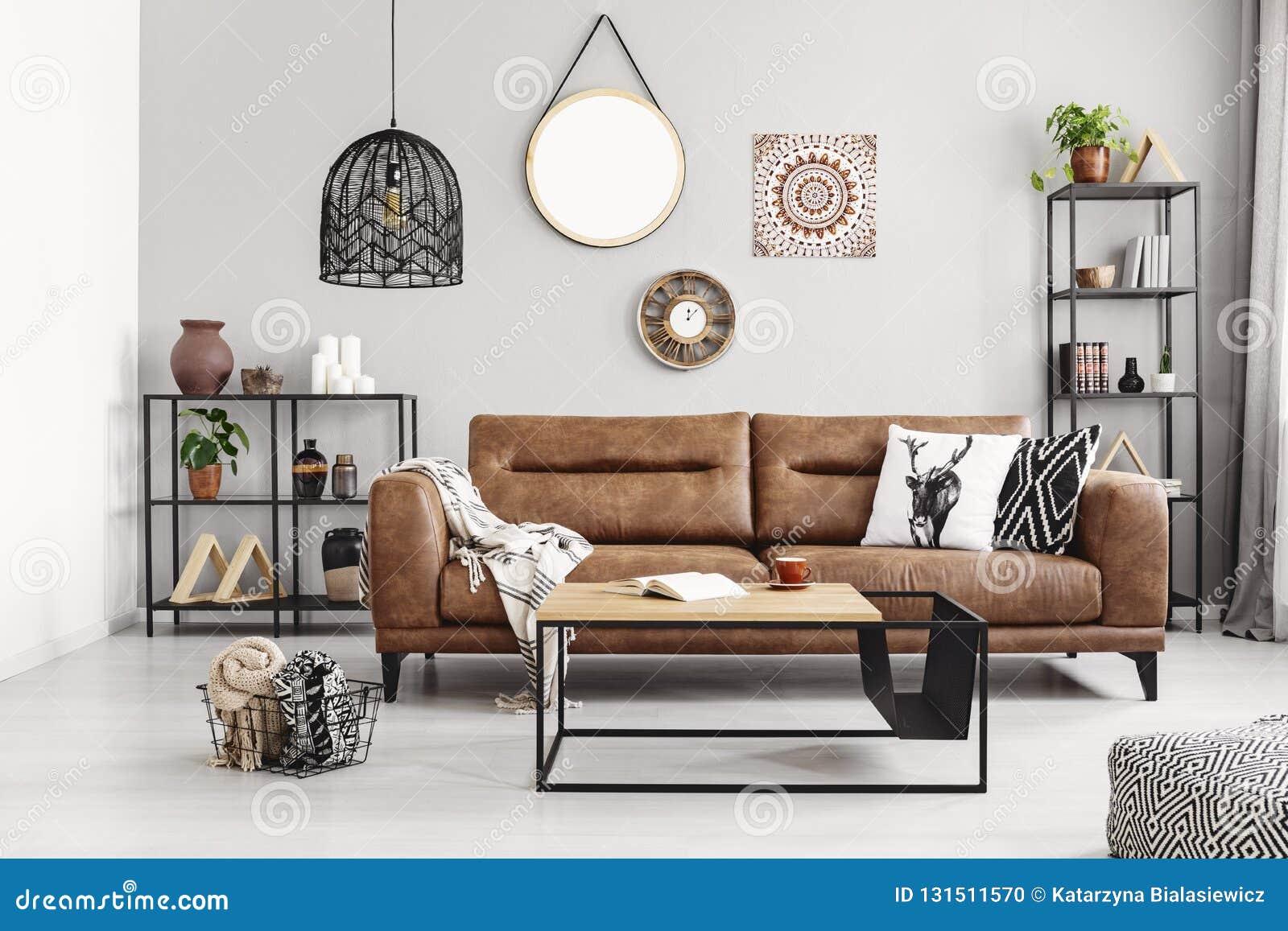 Sofá de cuero con las almohadas y la manta en la sala de estar elegante interior con los estantes del metal y la mesa de centro m