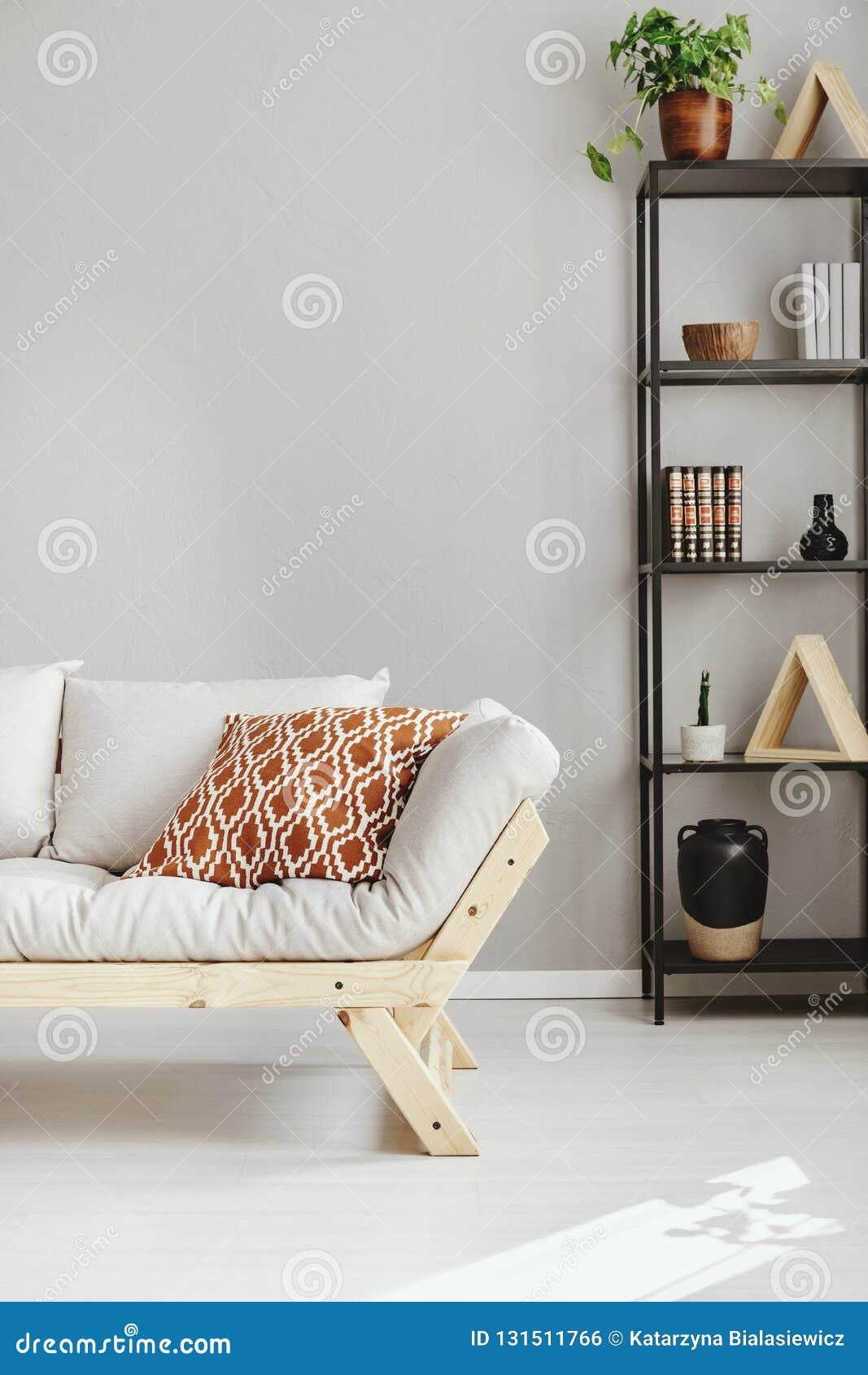 Sofá escandinavo al lado del estante con el diferente tipo de accesorios, foto real con el espacio de la copia