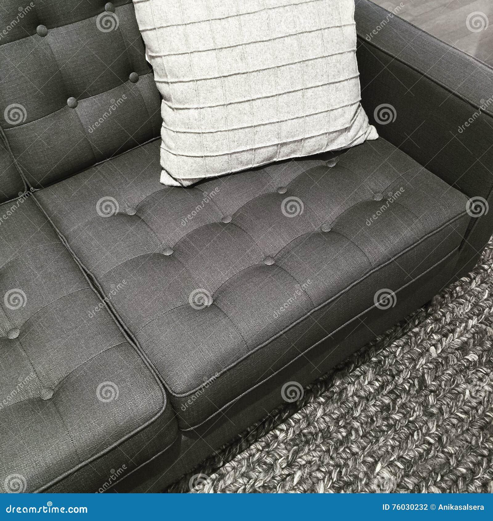 Sofá, manta y amortiguador en las sombras del gris