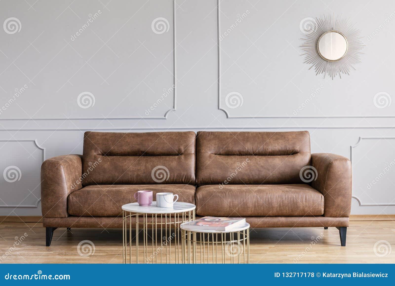 Sofá, mesas de centro y espejo de cuero en un interior de la sala de estar