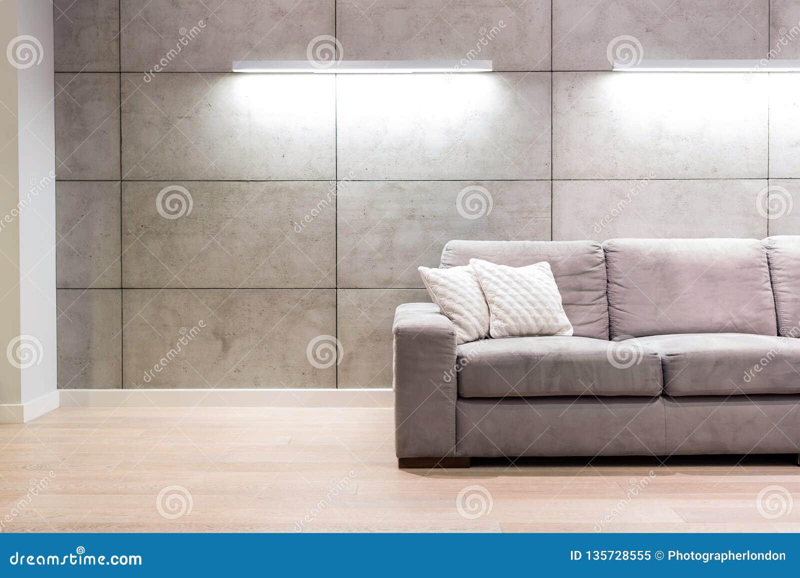 Sofá vazio contra a parede iluminada no apartamento