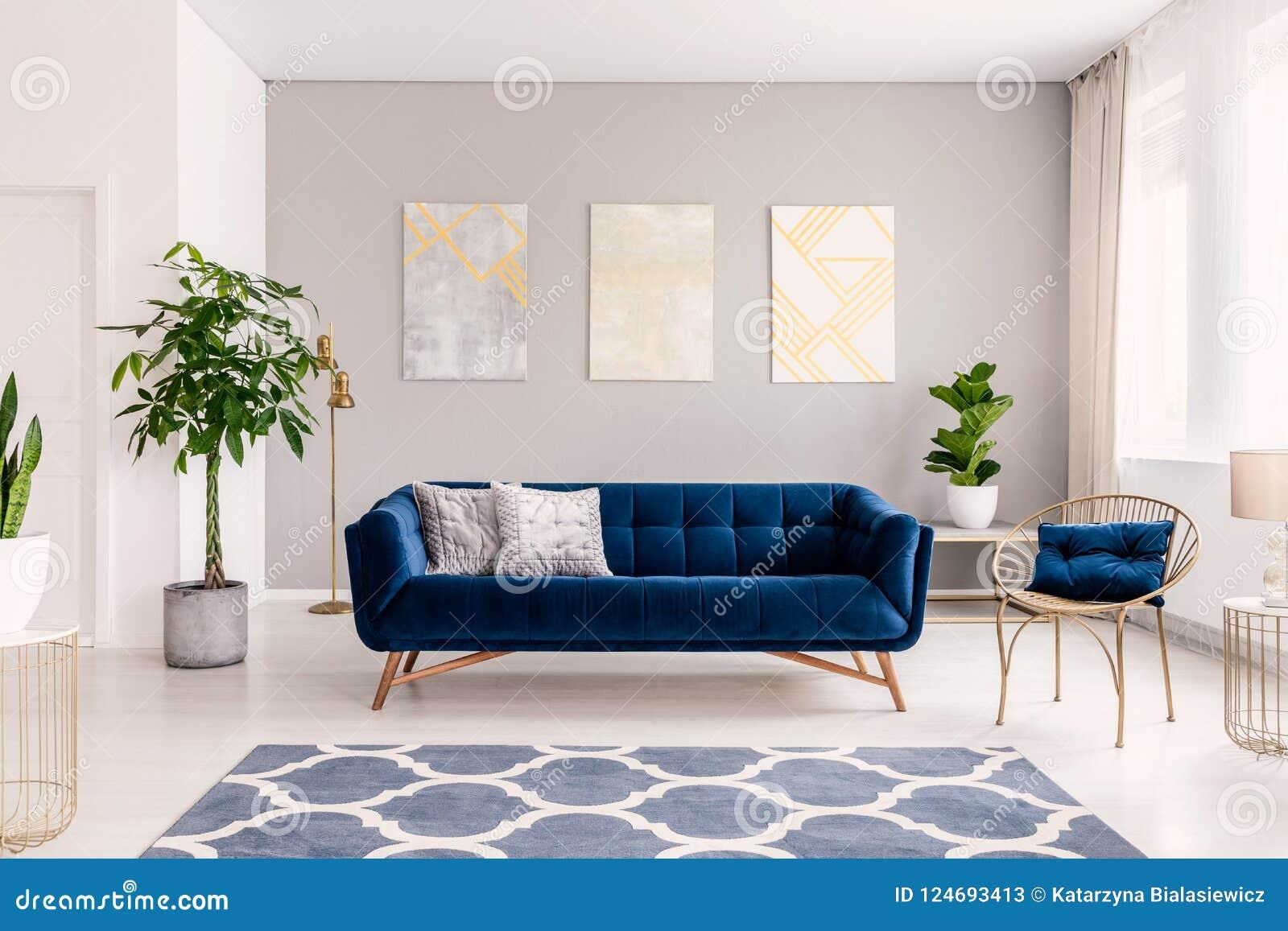 Soffa för kungliga blått med två kuddar som står i verkligt foto av den ljusa vardagsruminre med nya växter, fönster med gardiner