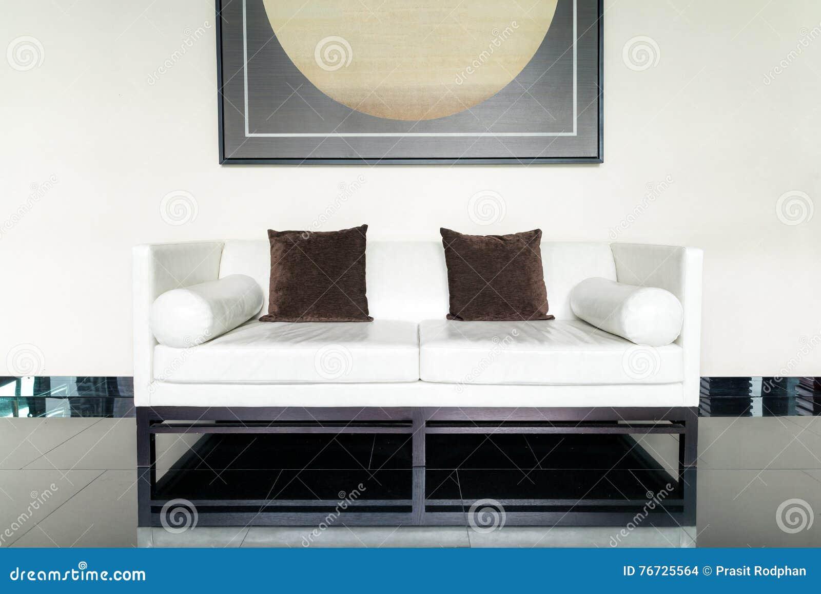 Soffa för vitt läder och brun kudde i vardagsrum på vardagsrum ...