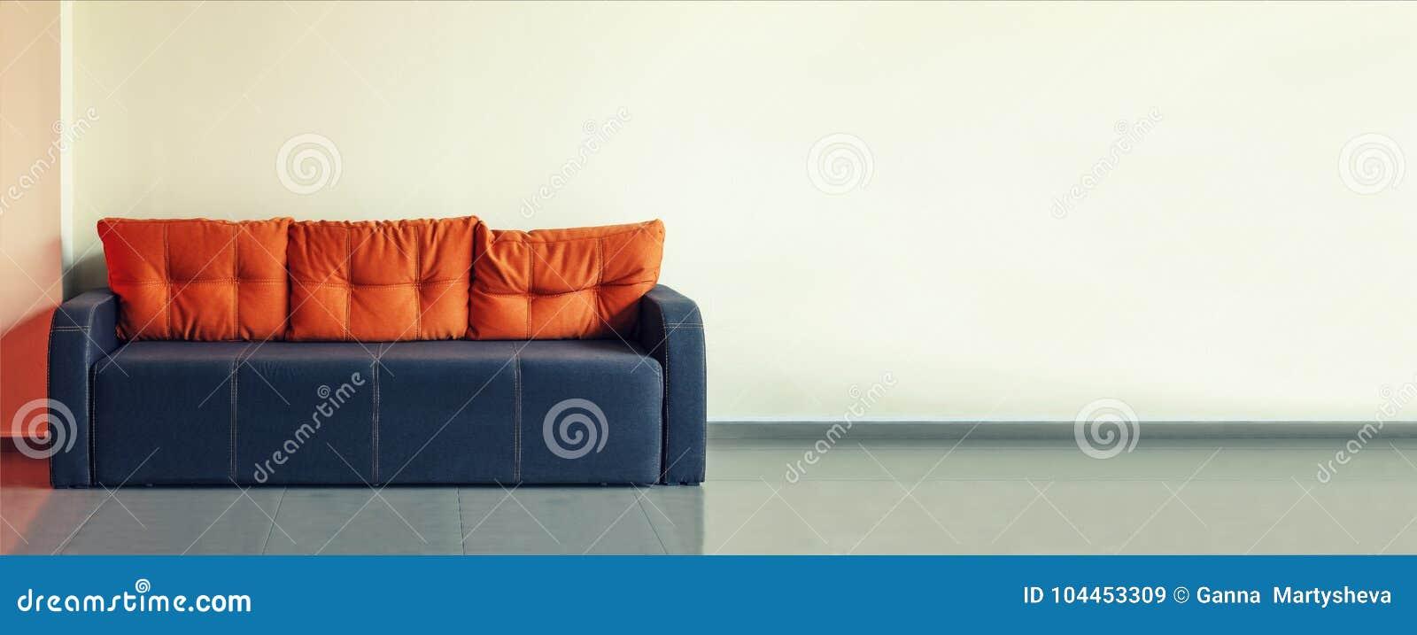 Soffa inredesign, kontor Tomt väntande rum med en modern blå soffa med guling dämpar framme av dörren och en klocka på
