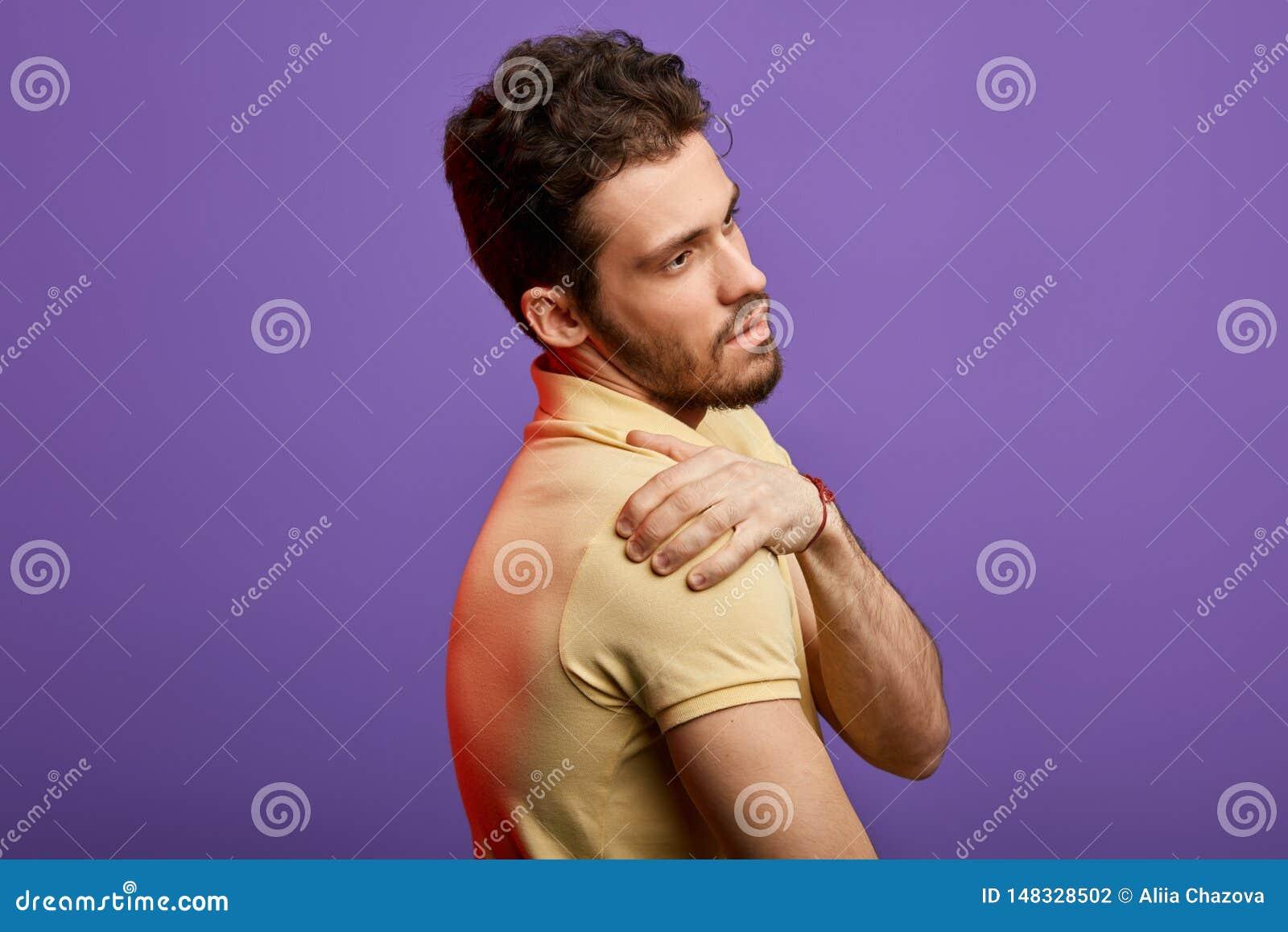 Sofferenza attraente dell uomo dal dolore nella sua spalla