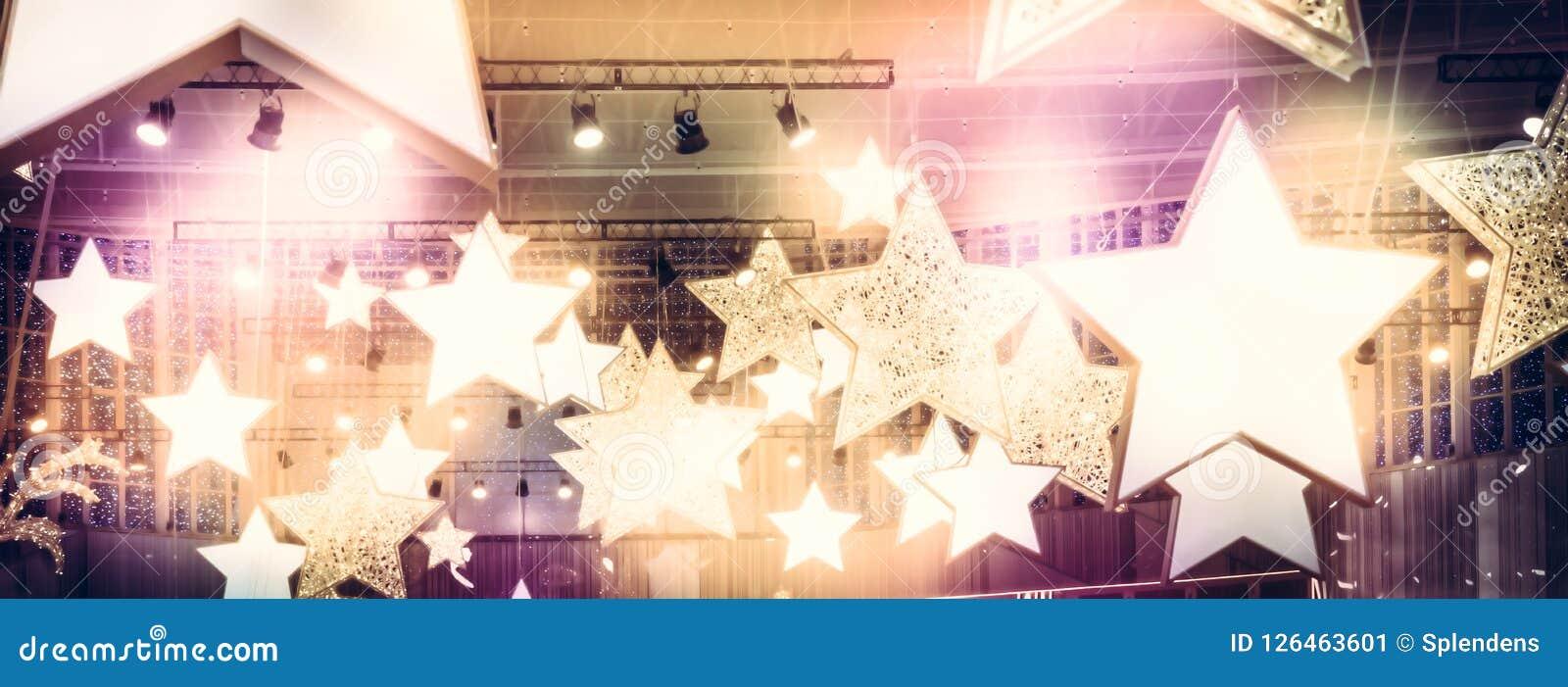 Soffits van sterrenschijnwerpers als fijnste uurberoemdheid tonen de achtergrond van stadiumprestaties met gouden roze lichten