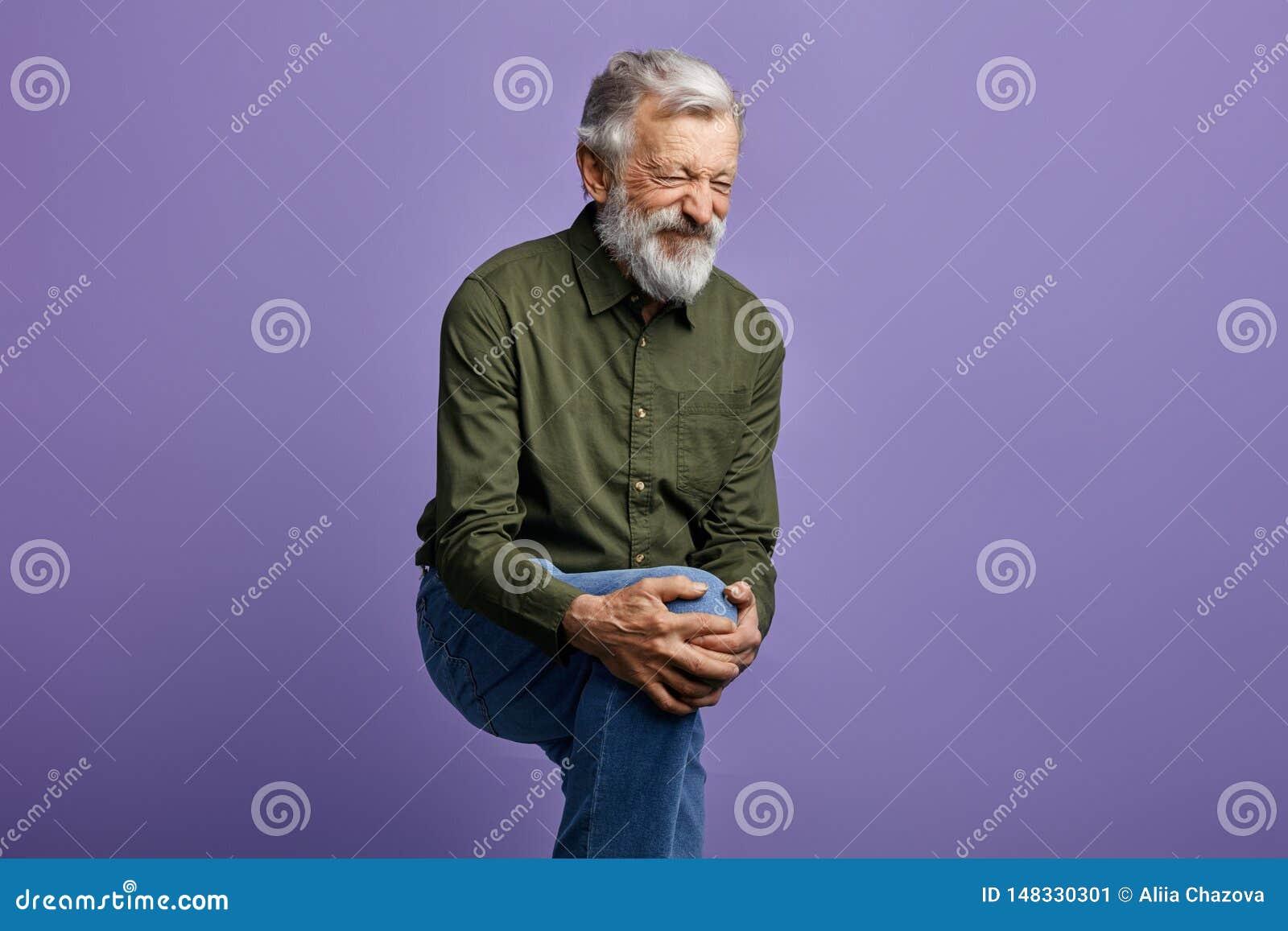 Sofrimento do ancião da dor do joelho isolada no fundo azul