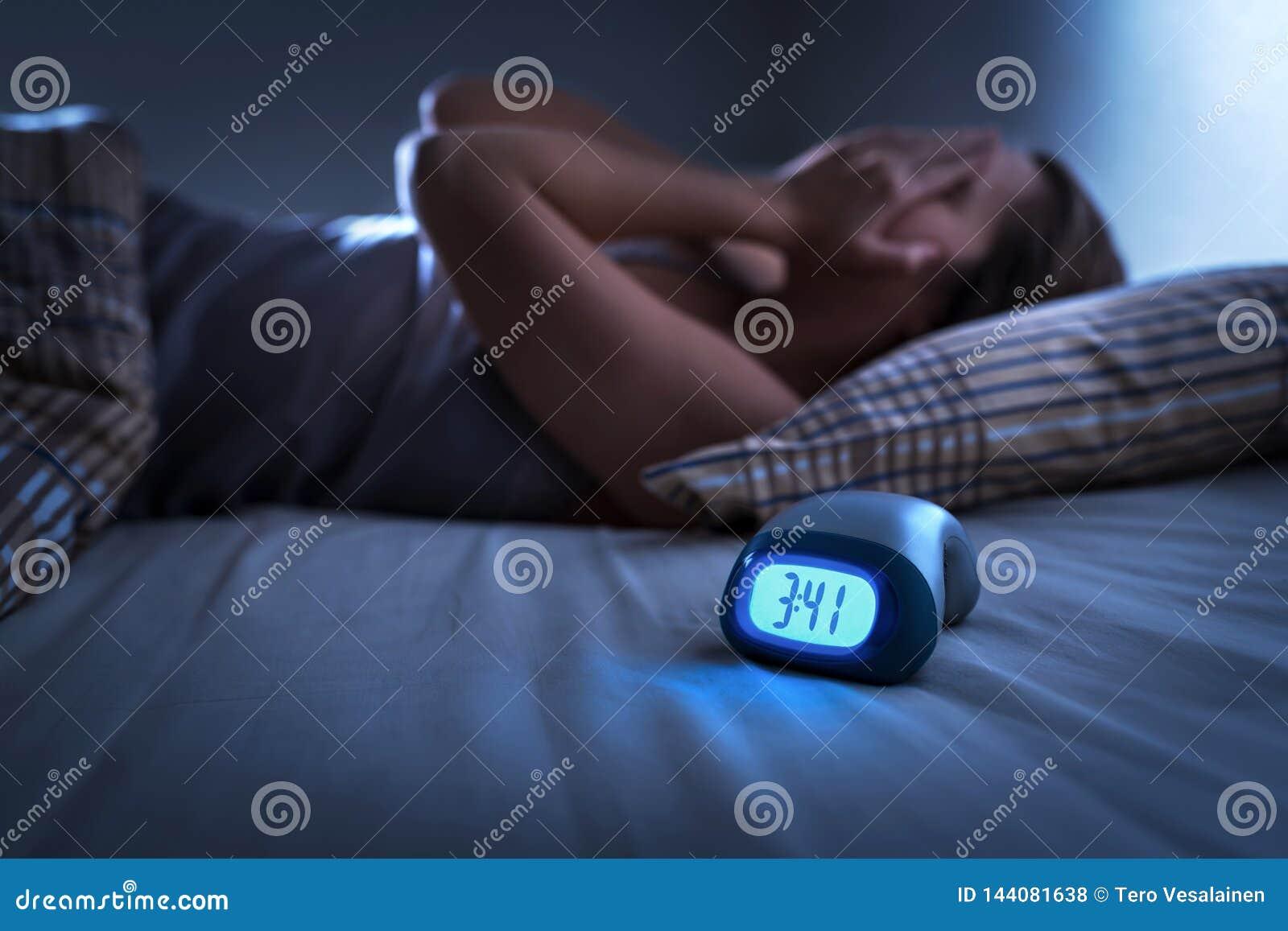 Sofrimento sem sono da mulher da insônia, da apneia do sono ou do esforço Senhora cansado e esgotada Dor de cabe?a ou enxaqueca