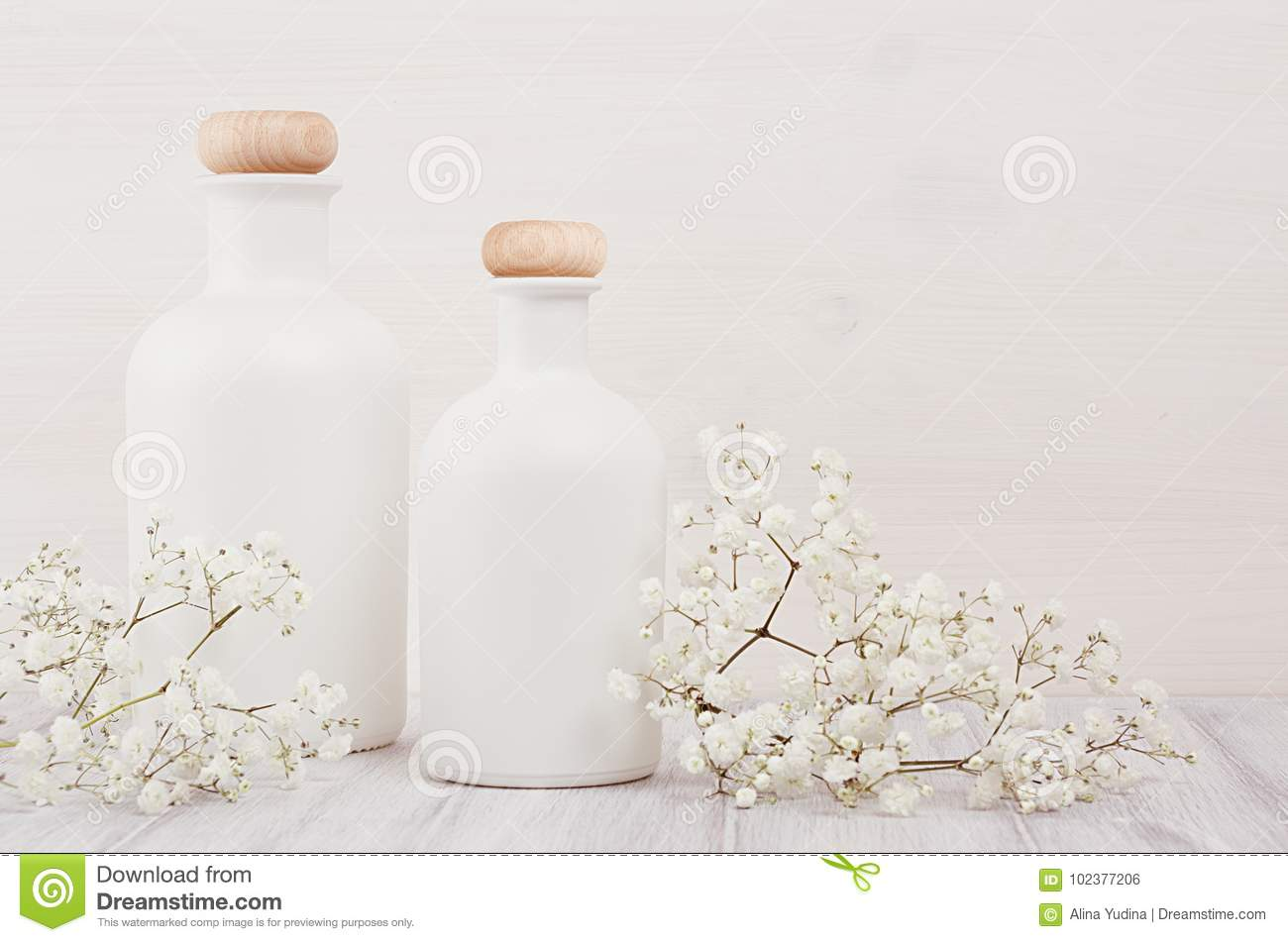 Soft elegant home decor with white bottles and small flowers on white wooden plank for advertising, designers, branding identity,