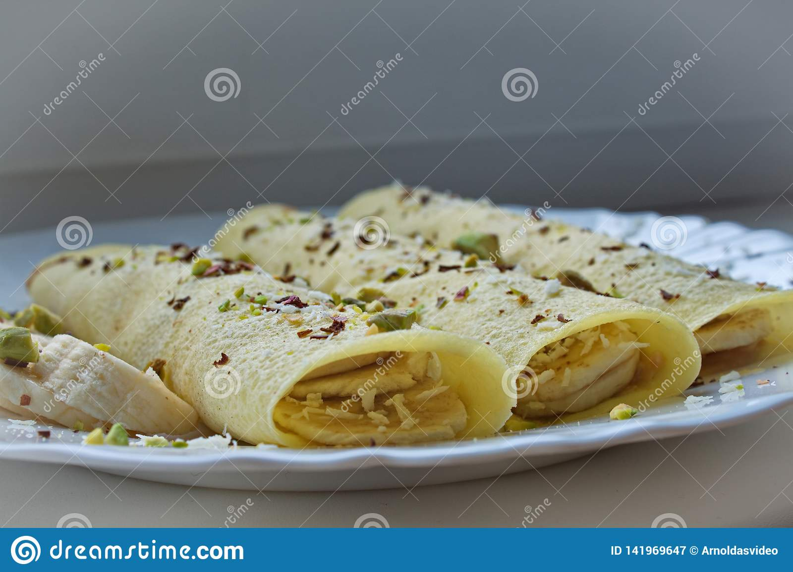 Soft focus close up of 3 crepes pancakes with peanut butter and bananas topped with chocolate and cocos shavings and pistachios