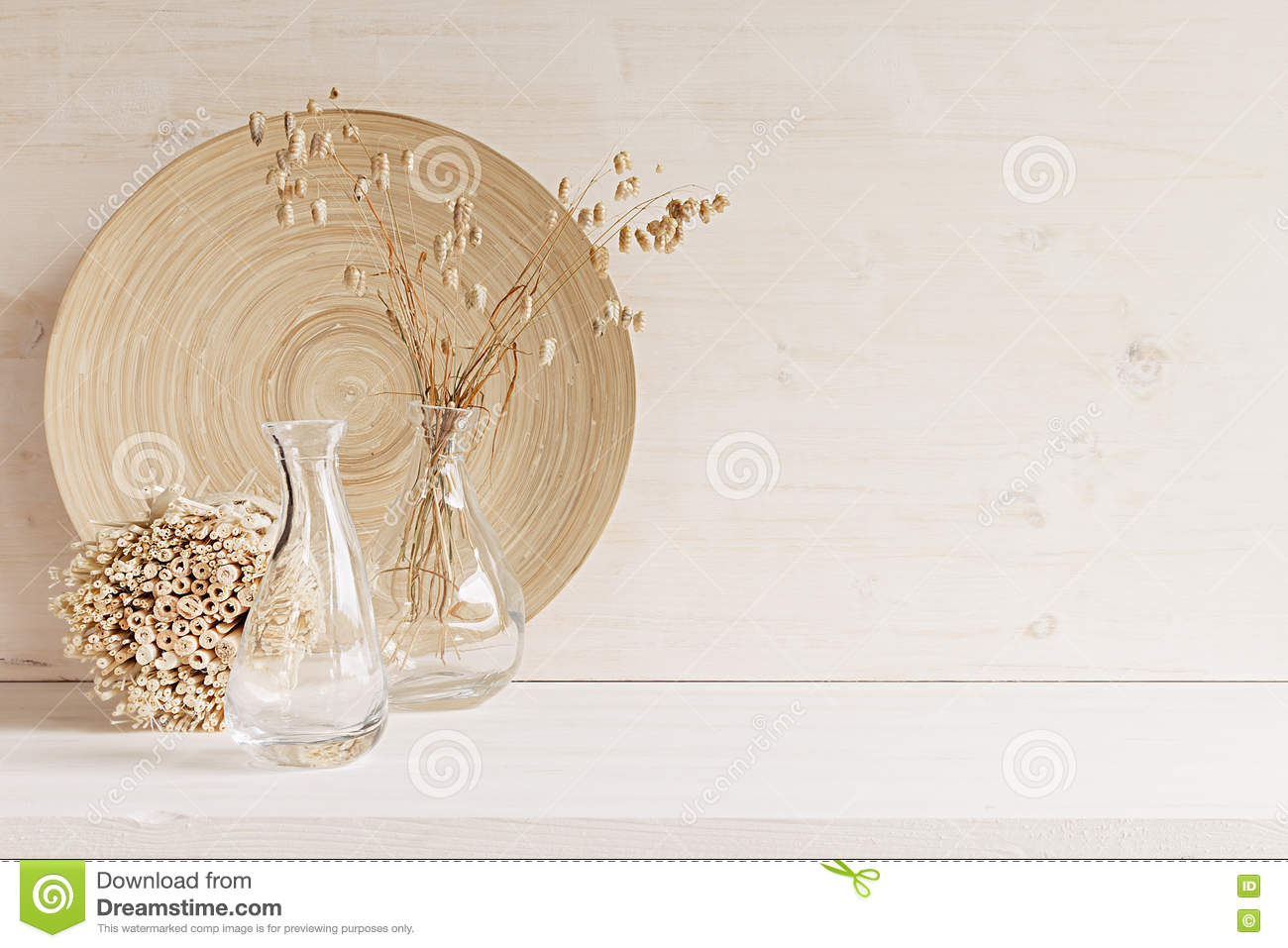 Soft home decor of glass vase with spikelets and wooden plate on white wood background.