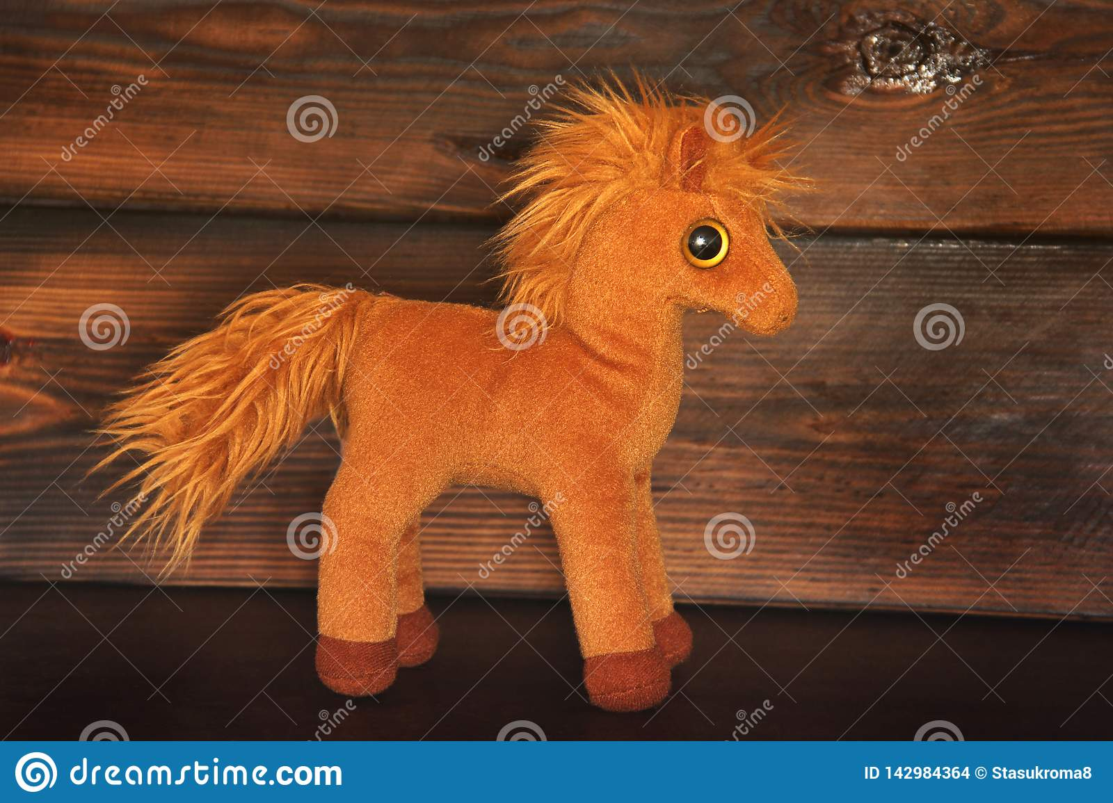 Soft toy on wooden background. Horse