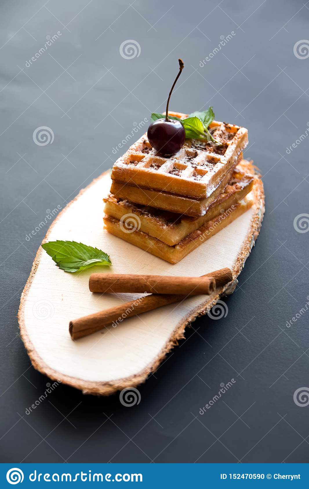 Soft waffles, on a black background, with cherries