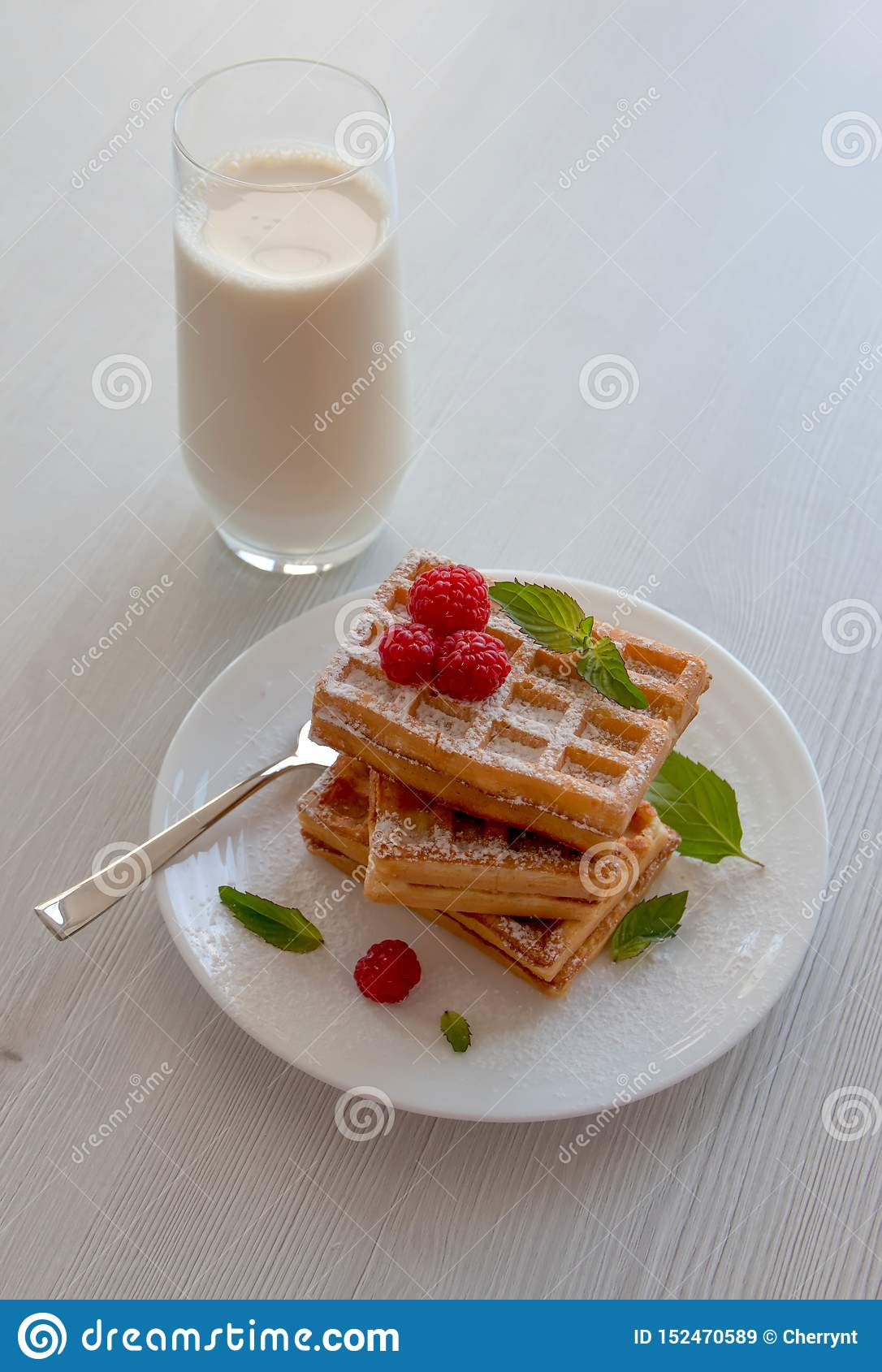 Soft waffles with raspberries and a glass of milk, on a white background