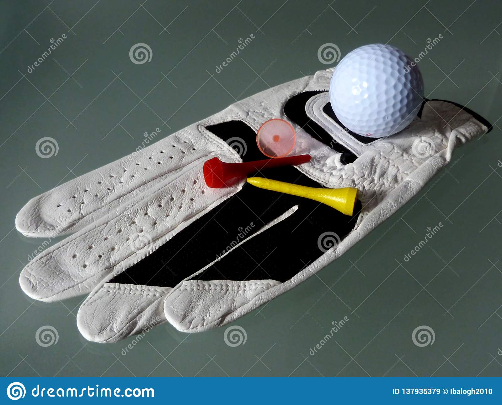 White leather golf glove close-up with tee and marker peg.