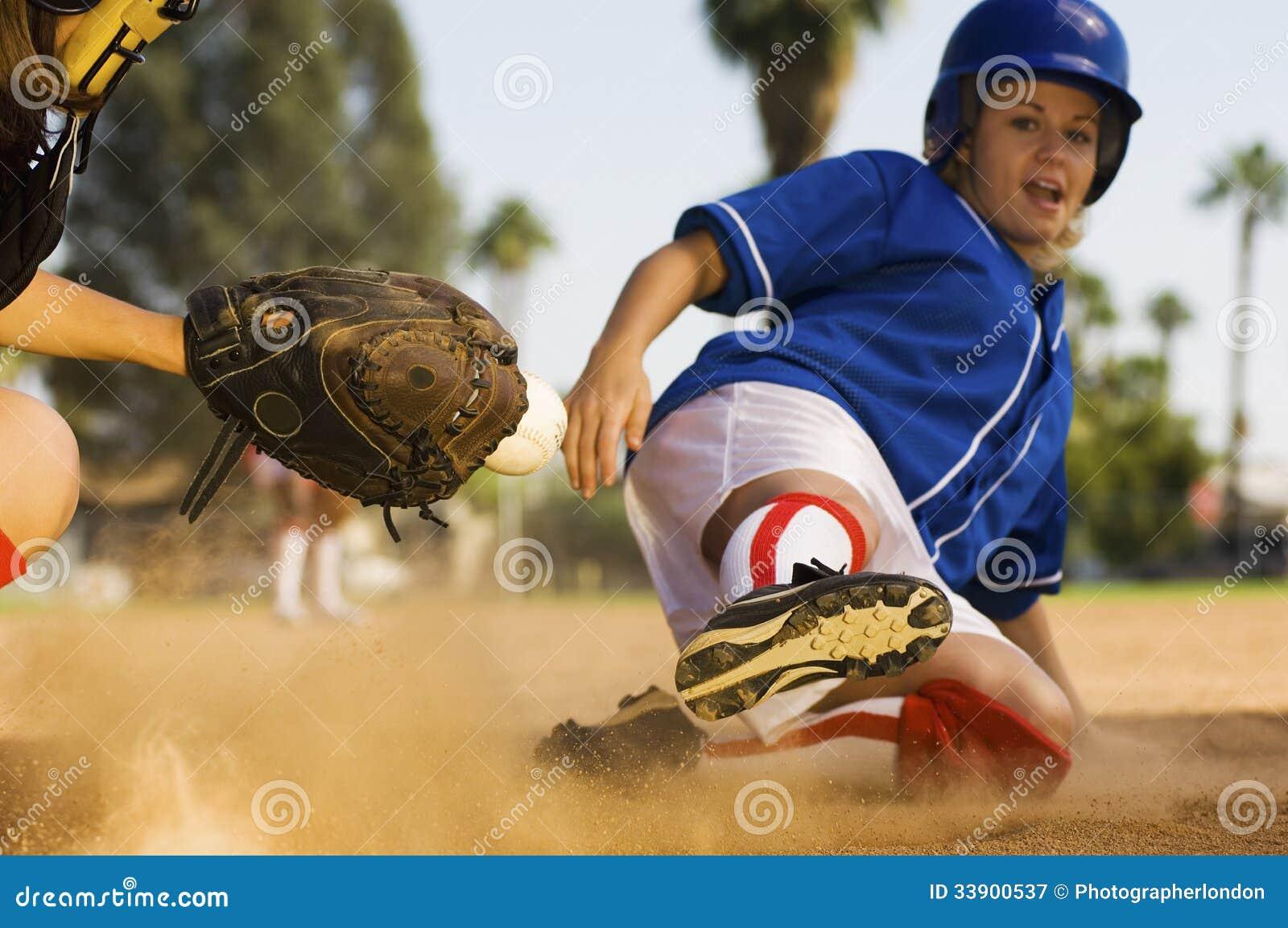 Softballspelare som glider in i den hem- plattan