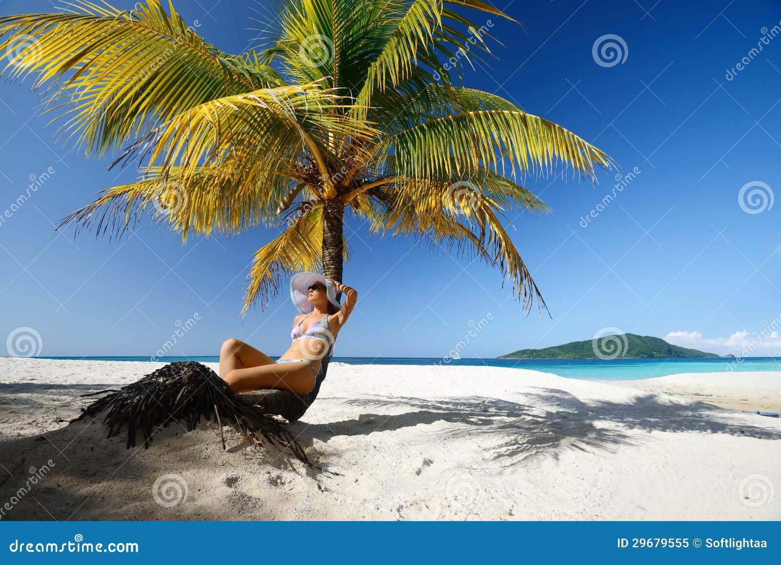 Sogno della donna che si siede sulla spiaggia sotto una palma su un beaut