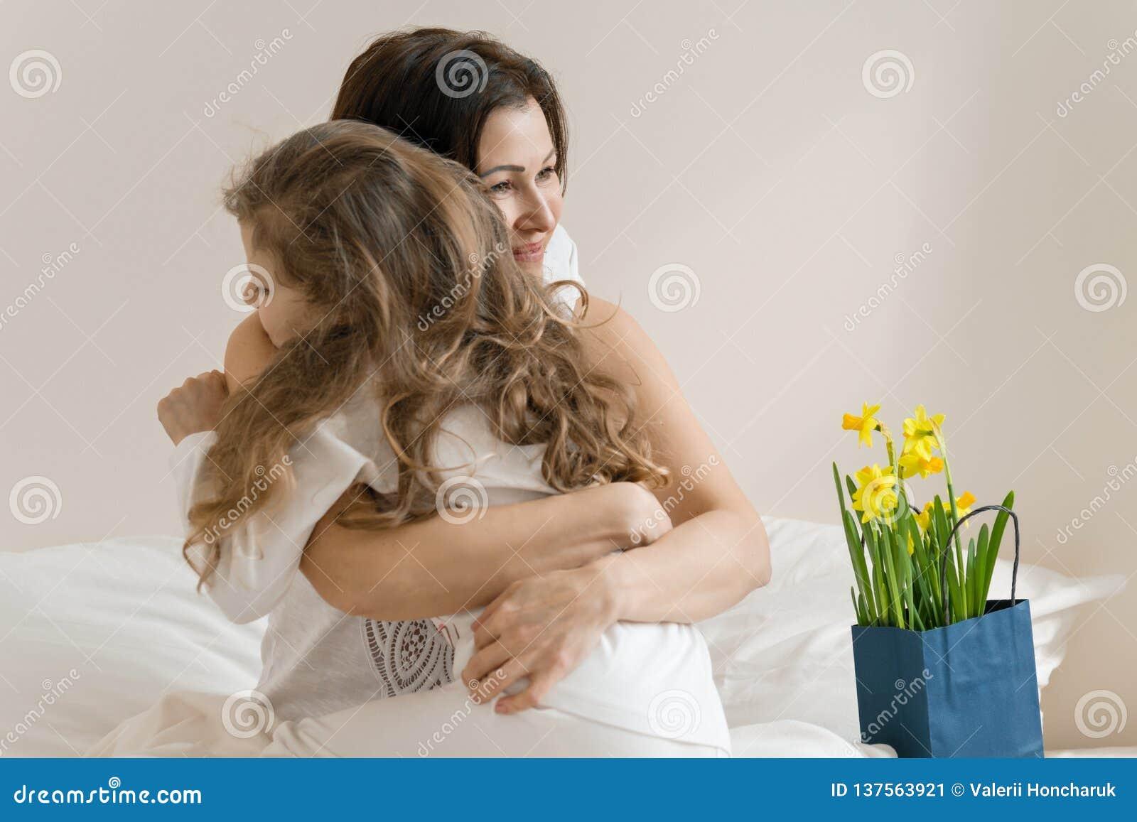 Sohn gibt der Mama eine Blume Morgen, Mutter und Kind im Bett, Mutter, die ihre kleine Tochter umarmt Hintergrundinnenraum des Sc