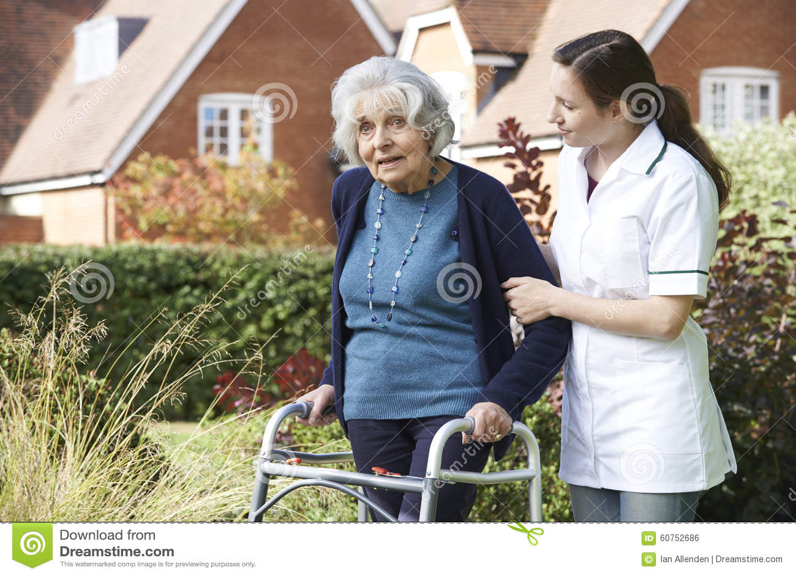 Soignant aidant l homme supérieur à marcher dans le jardin utilisant le cadre de marche