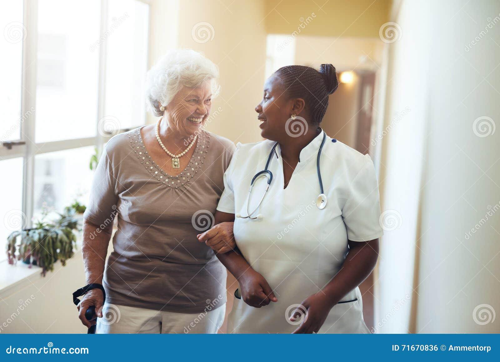 Soignez aider la femme supérieure à la femme de homeSenior de soins marchant dans la maison de repos soutenue par un travailleur