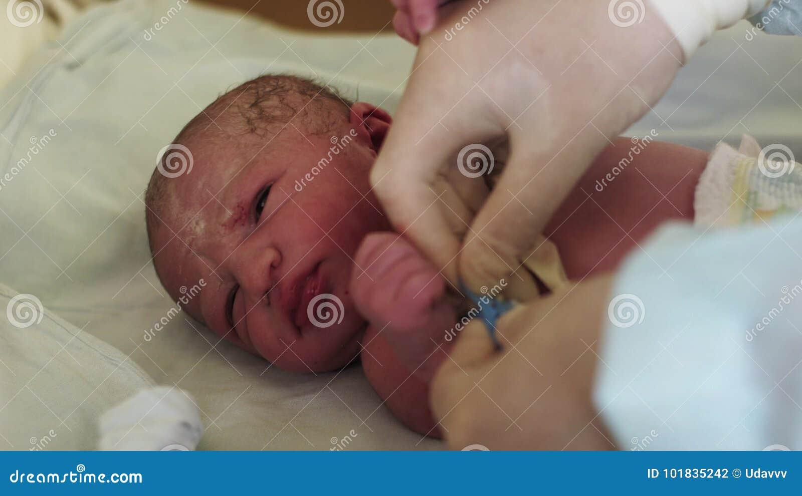 Soignez Dans Les Gants Mis Sur Le Bracelet Bleu En Main Du Bébé Nouveau,né  Hôpital De Maternité Enfant De Nouveau,né Banque De Vidéos , Vidéo du  people,
