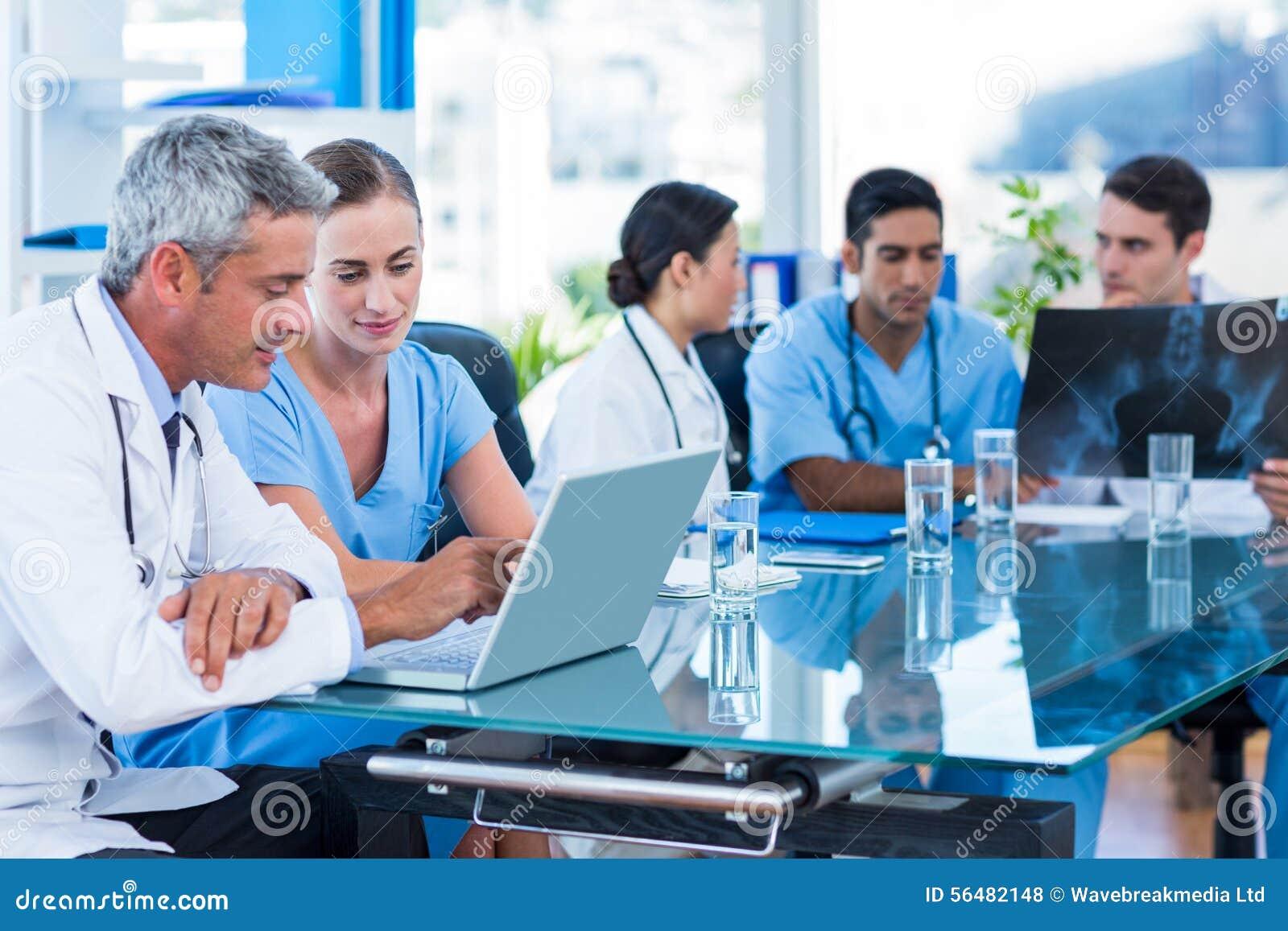 Soignez et soignez regarder l ordinateur portable avec des collègues derrière